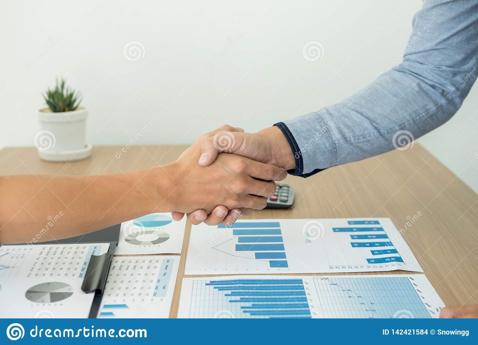 Dealing greeting and partnership meeting concept, businessmen handshaking after finishing up deal contract for both companies