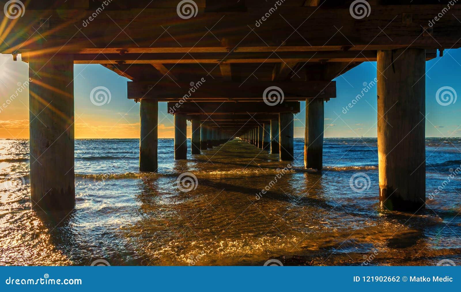 Debajo del embarcadero en la puesta del sol anaranjada de oro hermosa