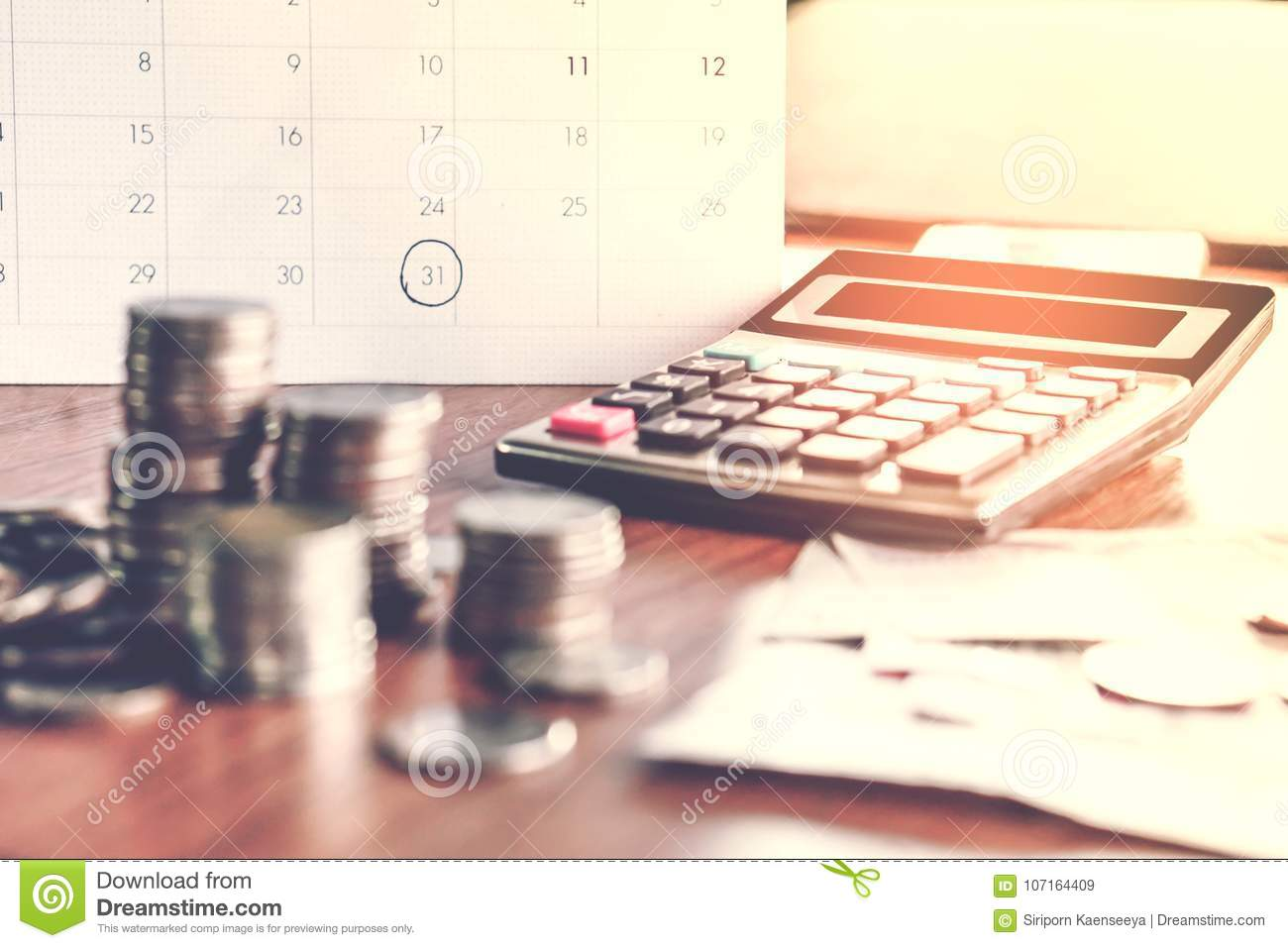 Debt collection and tax season concept with deadline calendar remind note,coins,banks,calculator on table