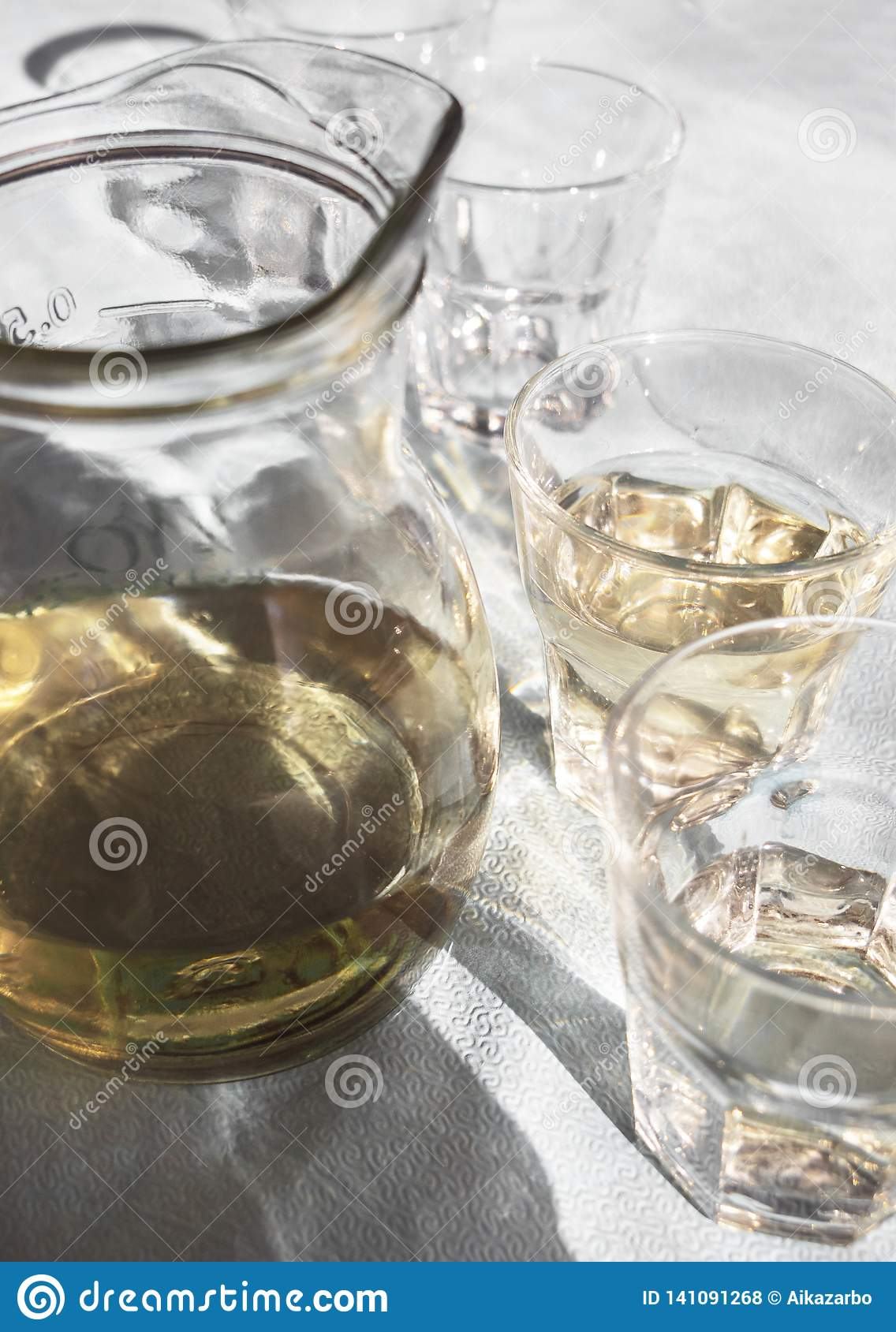 Decanter and glasses filled with homemade white Greek wine, on the table in a tavern in the sunlight and with beautiful shadows