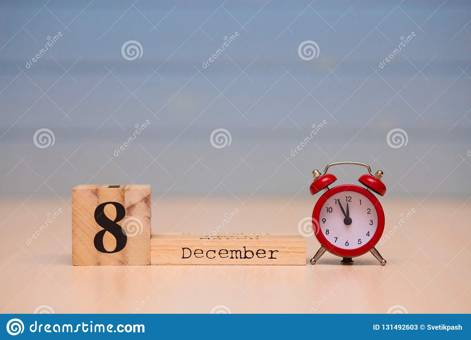 December 8th set on wooden calendar and red alarm clock with blue background