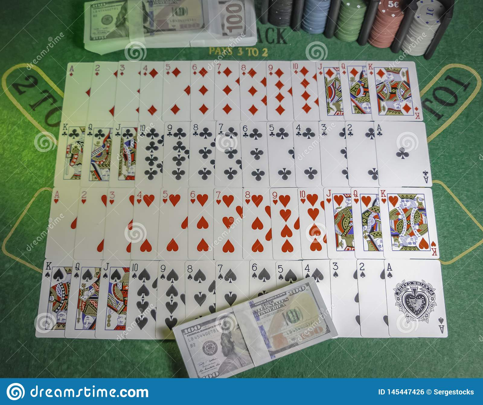 Deck of playing cards, Casino chips and pack of 100s of US dollars on the green table for Blackjack lighted with party lights