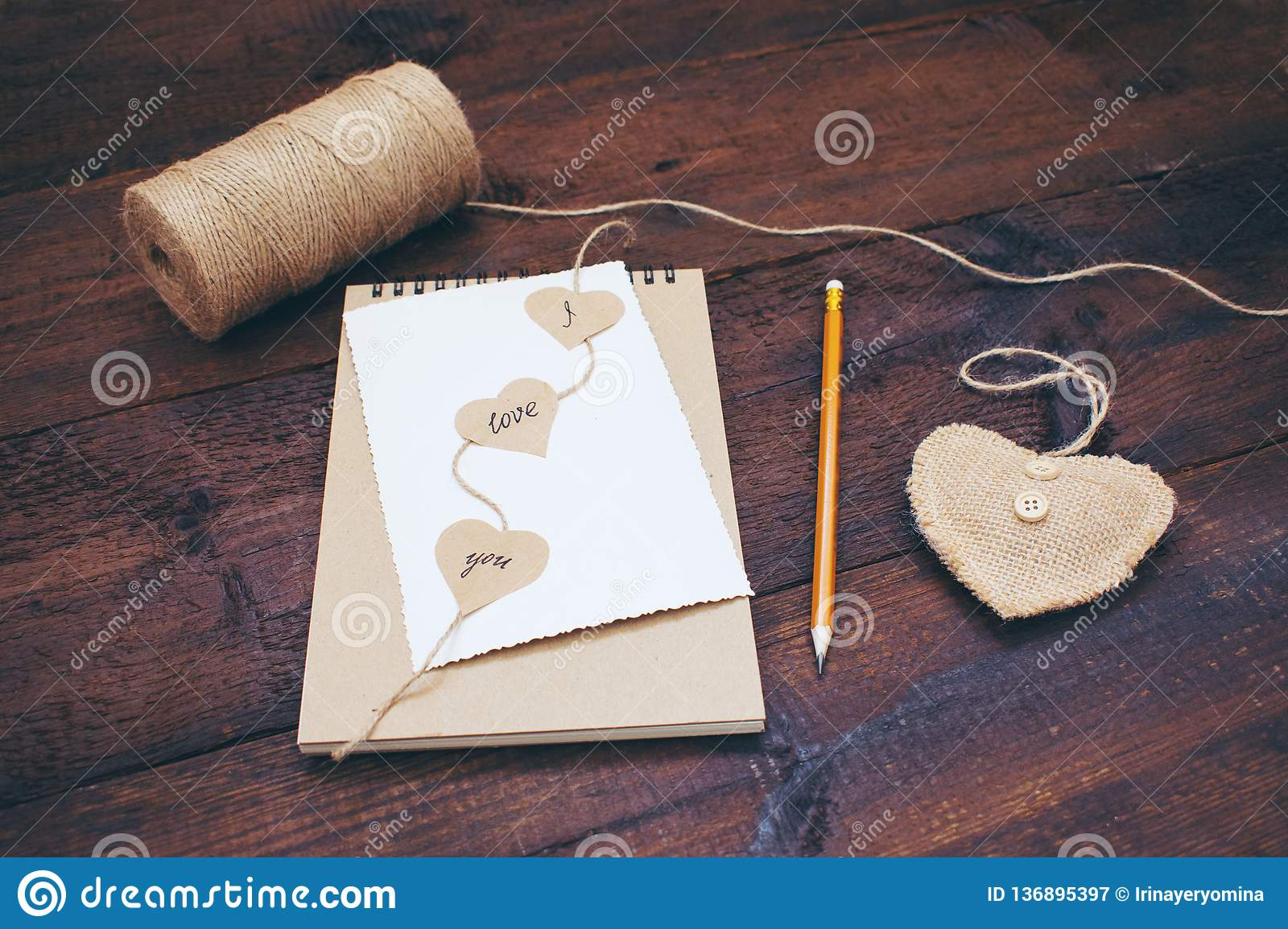 Declaration of love. Valentines day craft card ideas. Greeting card with text I LOVE YOU on craft recycled paper notebook, pencil