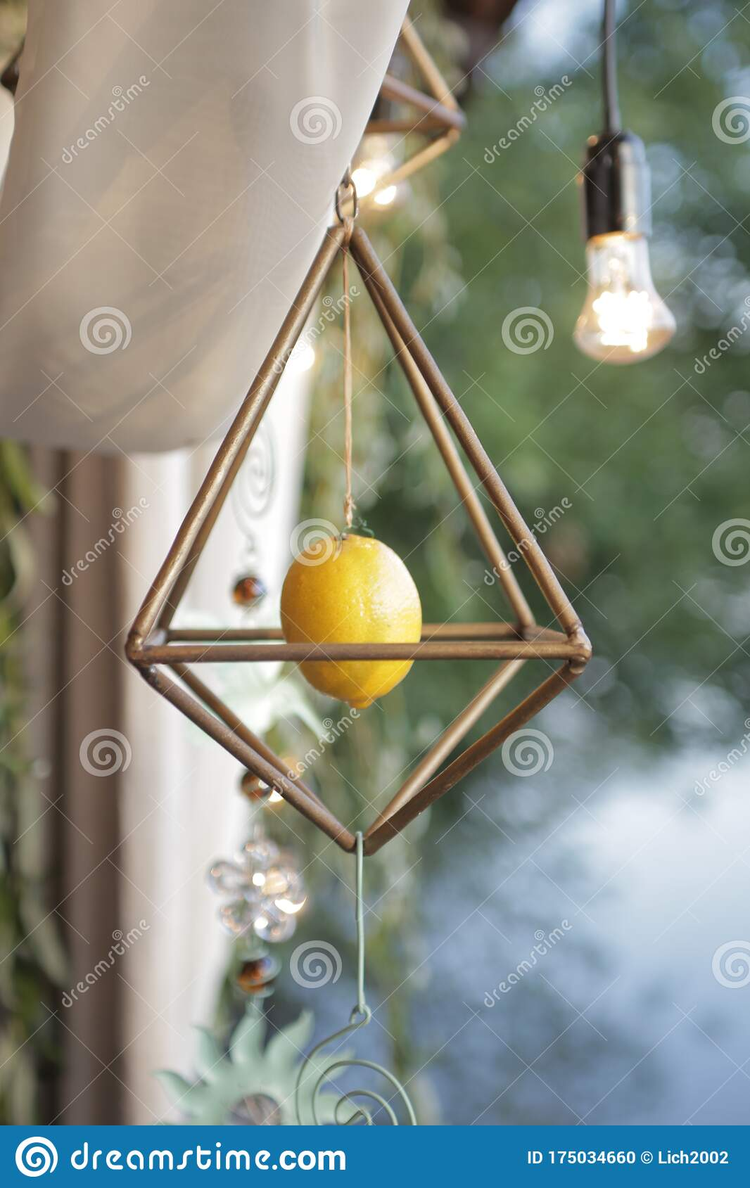 Decor In The Form Of A Lemon In A Suspended Cage With Flower Pendants Stock Photo Image Of Metallic Bokeh 175034660