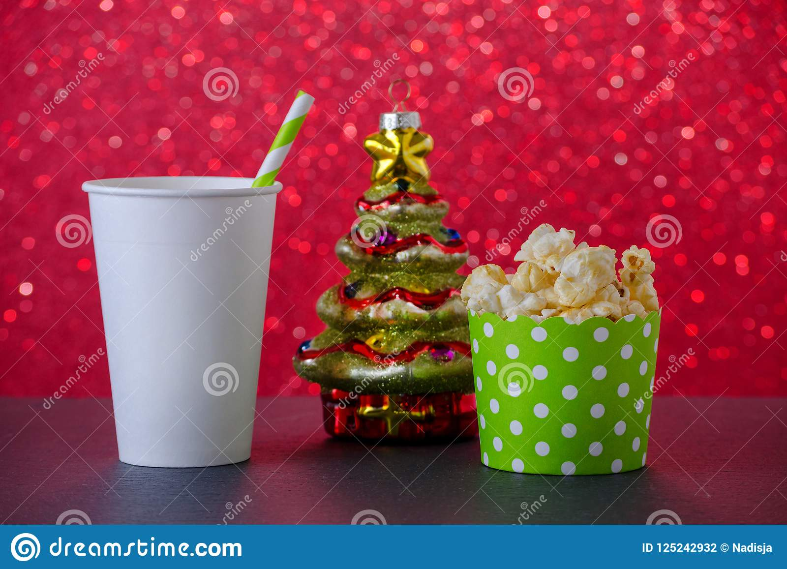 Decoração da árvore da pipoca, da bebida e de Natal para o filme no fundo vermelho do bokeh, foco seletivo