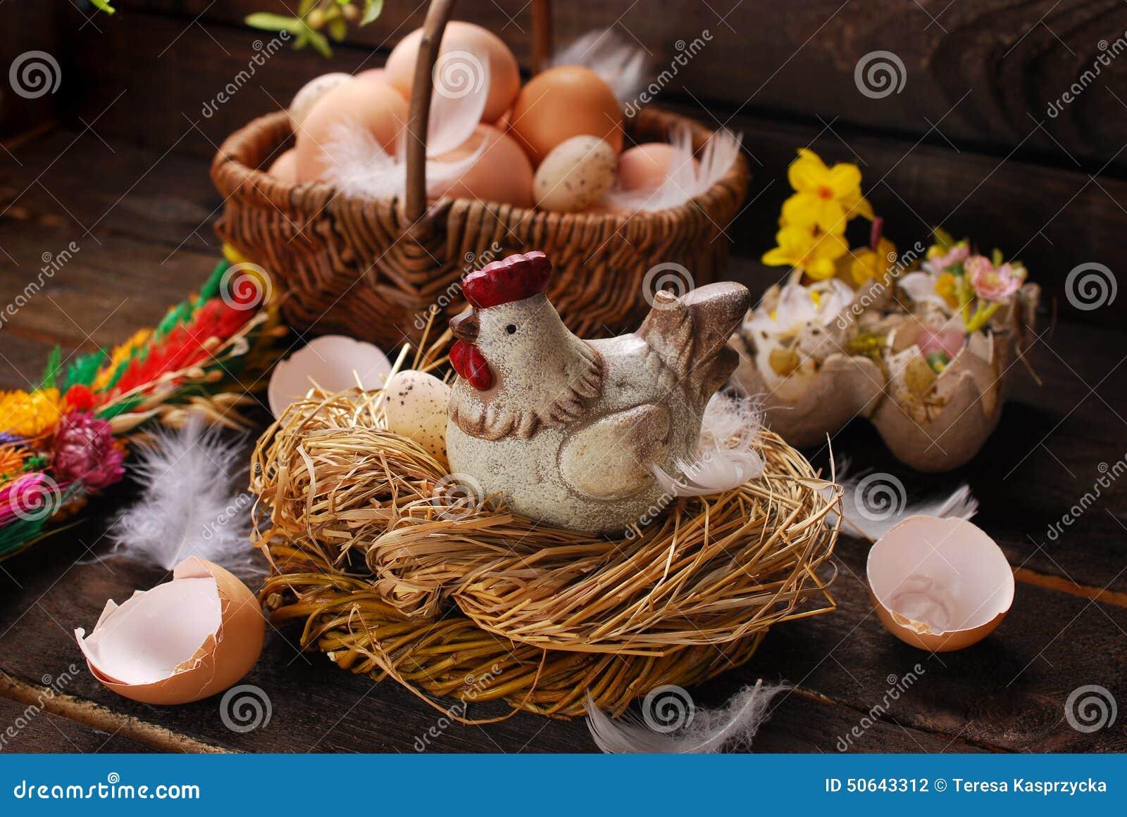 Decoração da Páscoa da galinha no ninho e da cesta de vime com ovos