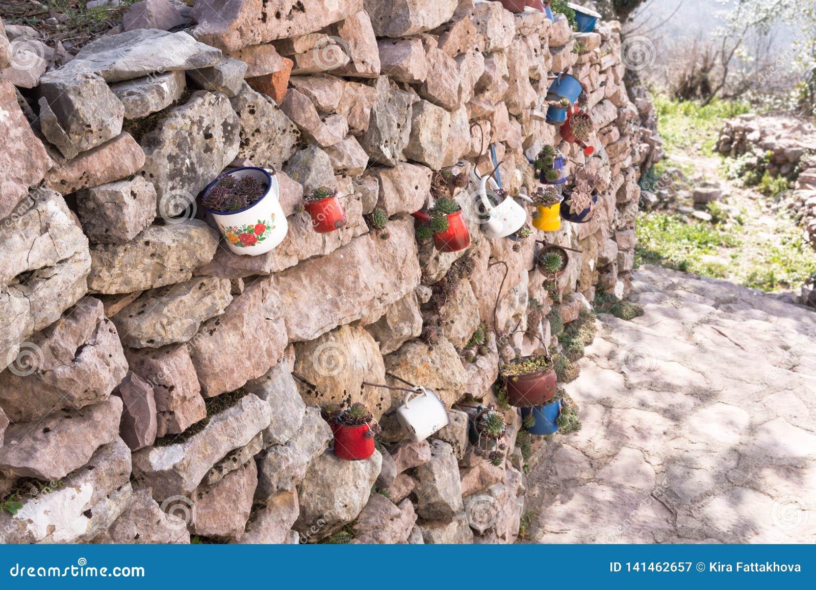 Decoração da parede de pedra do jardim com canecas do ferro, utensílios do ferro com flores Dia ensolarado