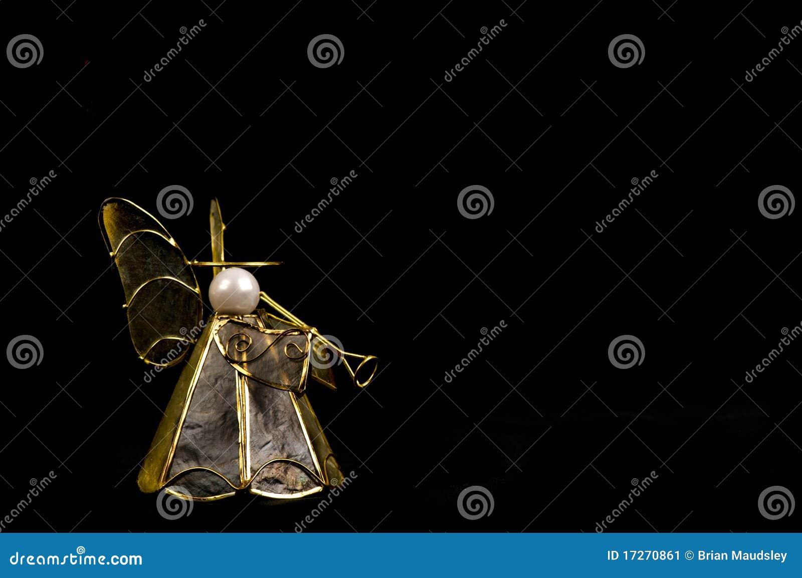Decoração do anjo do Natal com a trombeta no preto.