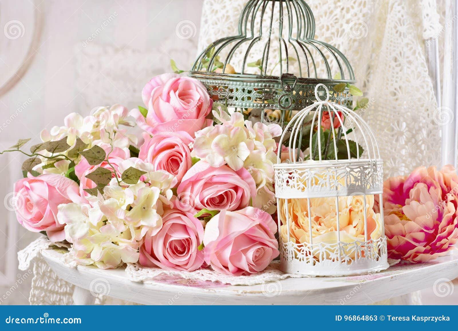 Decoração do estilo do vintage com as flores em gaiolas de pássaro velhas