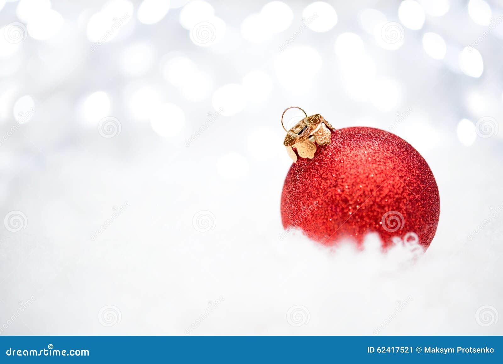Decoração do Natal com a bola vermelha na neve no fundo borrado com luzes do feriado ano novo feliz 2007