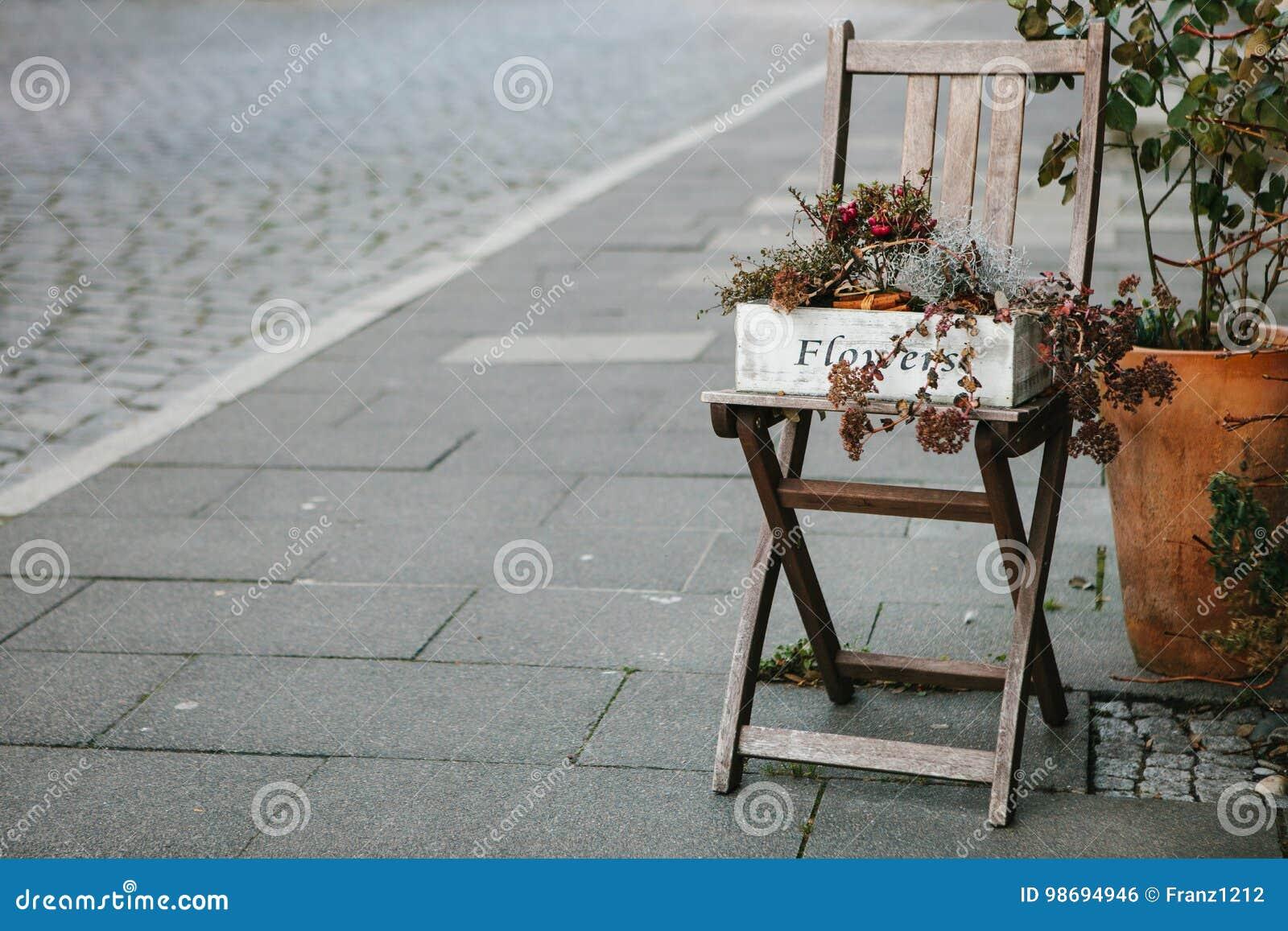 Decoração do outono com uma cadeira e flores na rua