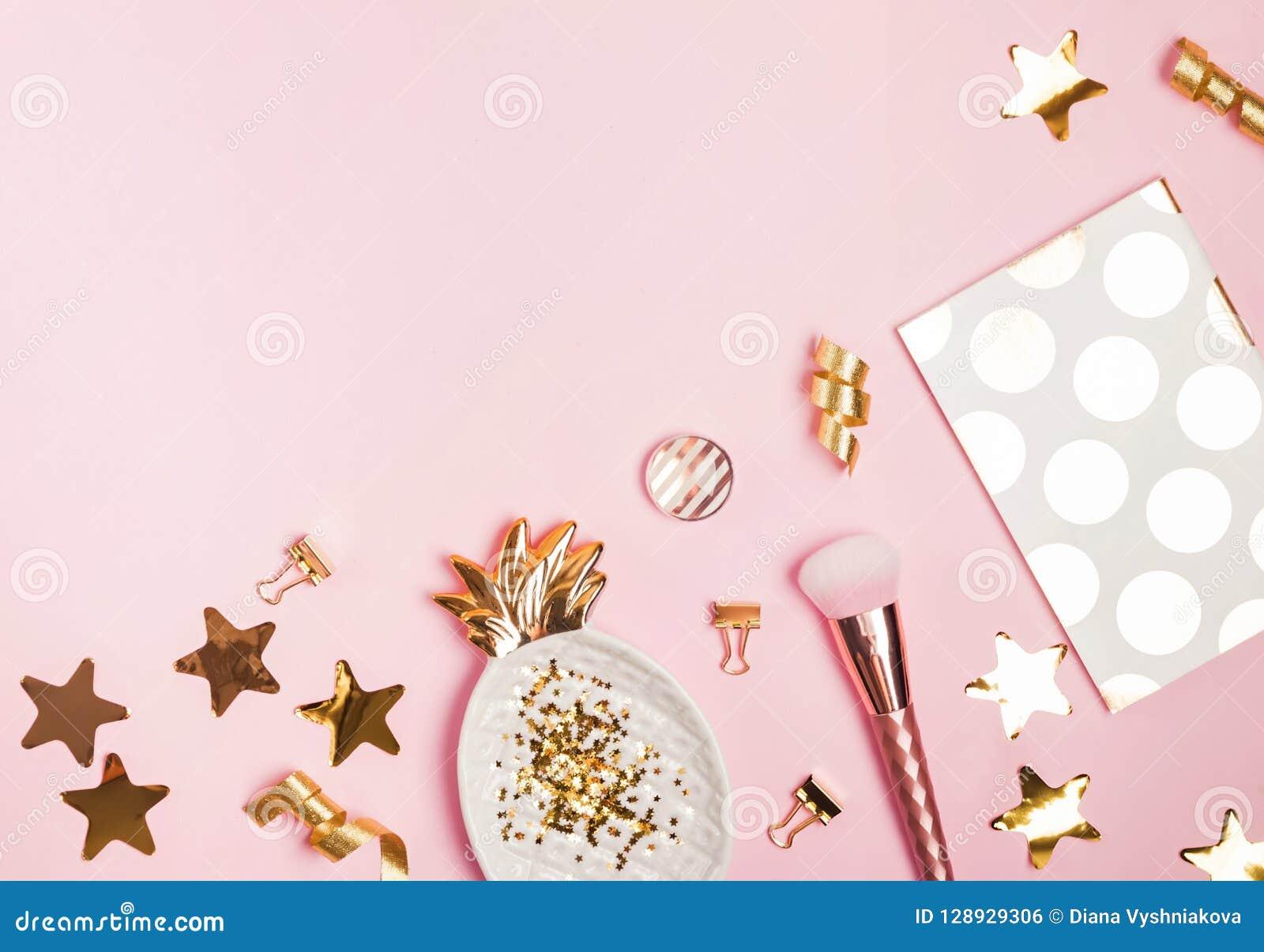 Decoração dourada e acessórios femininos no fundo cor-de-rosa,