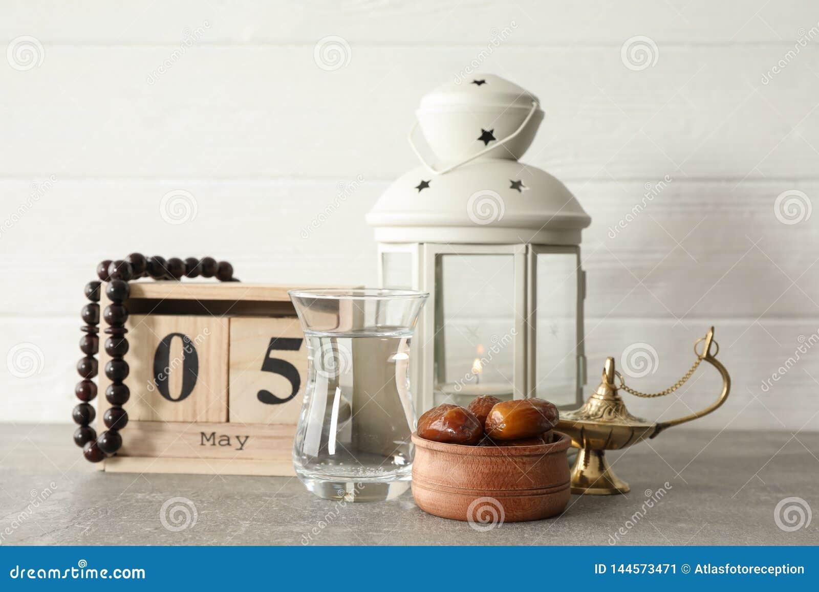 Decoração e alimento do feriado de Ramadan Kareem com o calendário na tabela cinzenta