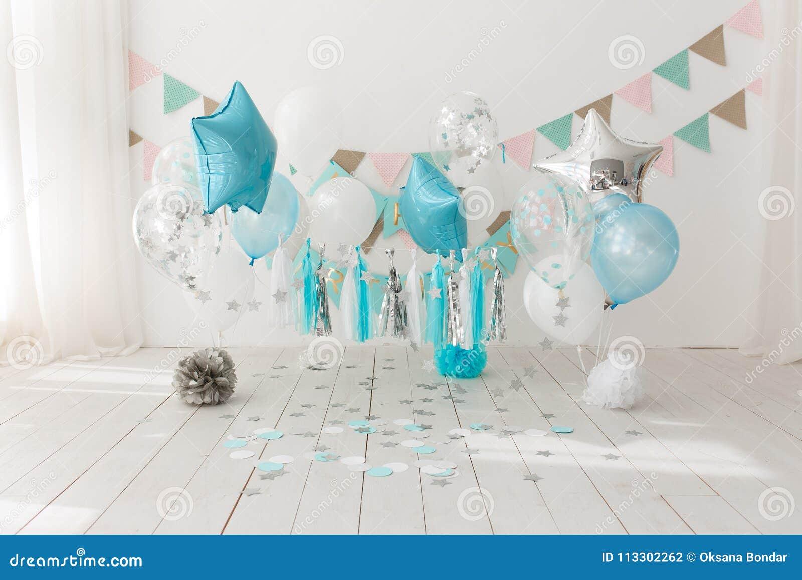 Decoração festiva do fundo para a celebração do aniversário com bolo gourmet e os balões azuis no estúdio, quebra do bolo primeir