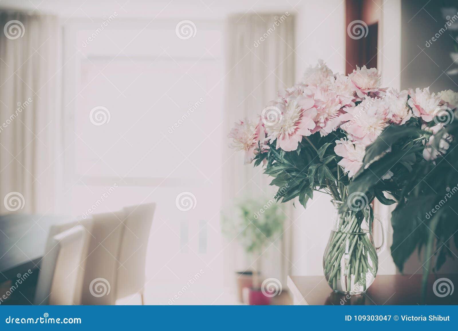 Decoração home com grupo cor-de-rosa fresco das peônias no vaso de vidro no fundo da sala de visitas, nostálgico retro