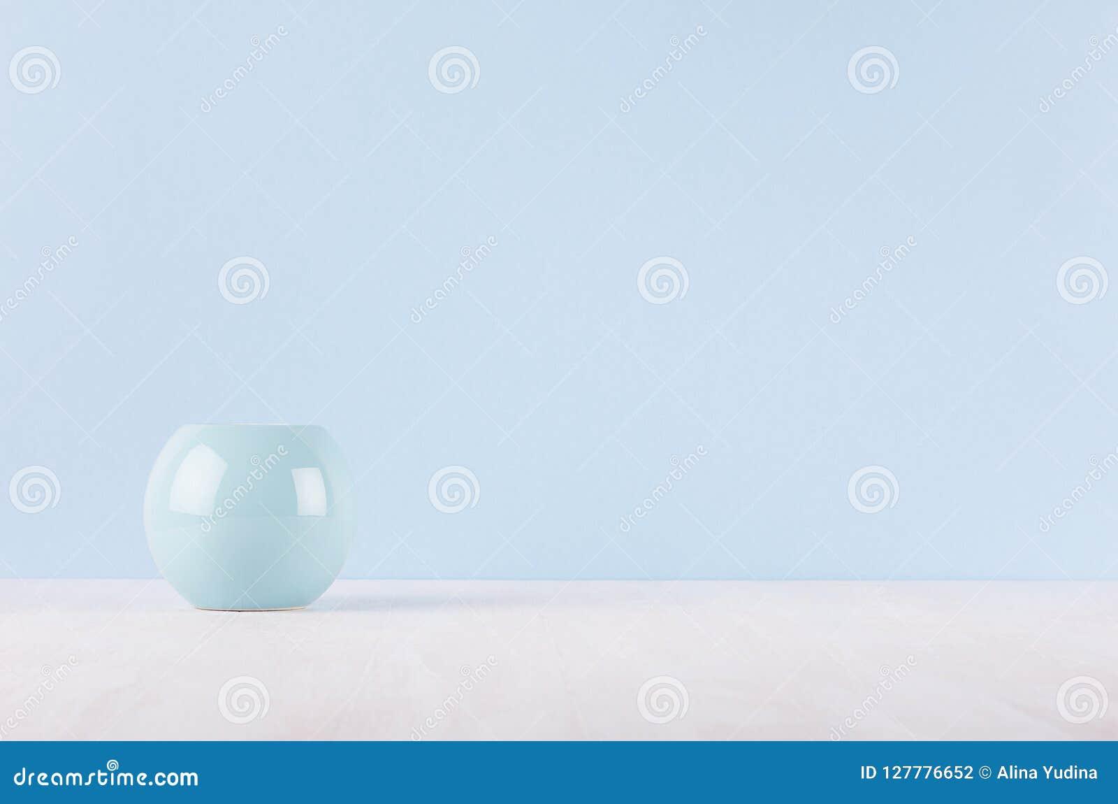 Decoração home moderna elegante do vaso cerâmico liso do círculo na tabela e na luz de madeira brancas - parede azul
