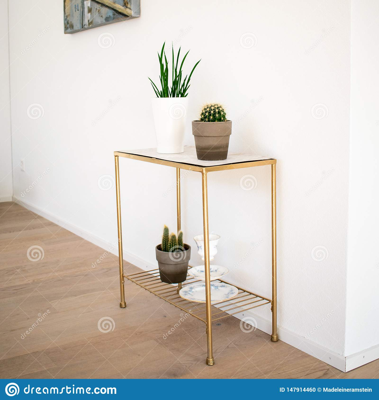 Decoração interior; tabela lateral do dourado-mármore com as plantas internas no assoalho de parquet