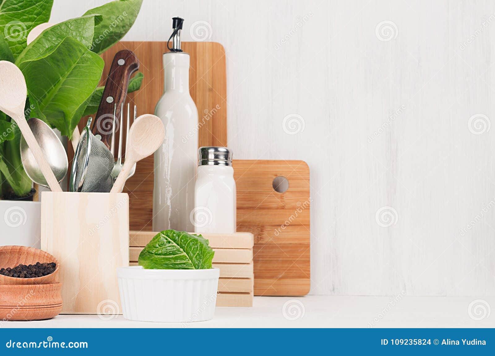 Decoração moderna da cozinha - utensílios de madeira bege, placas de corte marrons, planta verde no fundo de madeira branco da lu