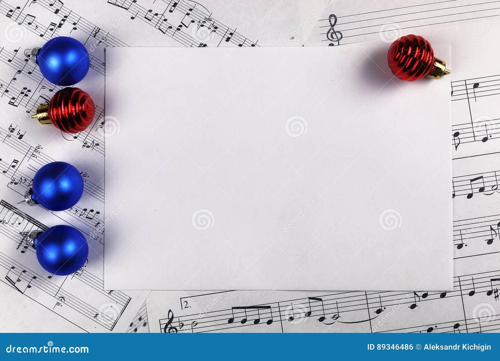 Decorações da árvore de Natal na tabela e na folha com música não