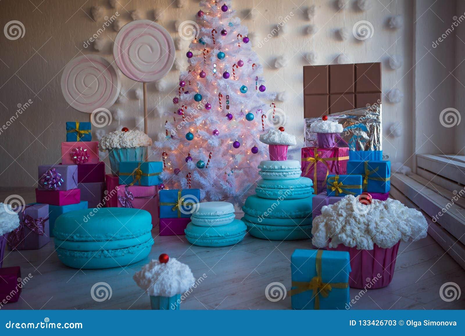 Decorações do Natal sob a forma dos bolos e do grande chocolate Brinquedos do Natal em uma árvore de Natal artificial branca