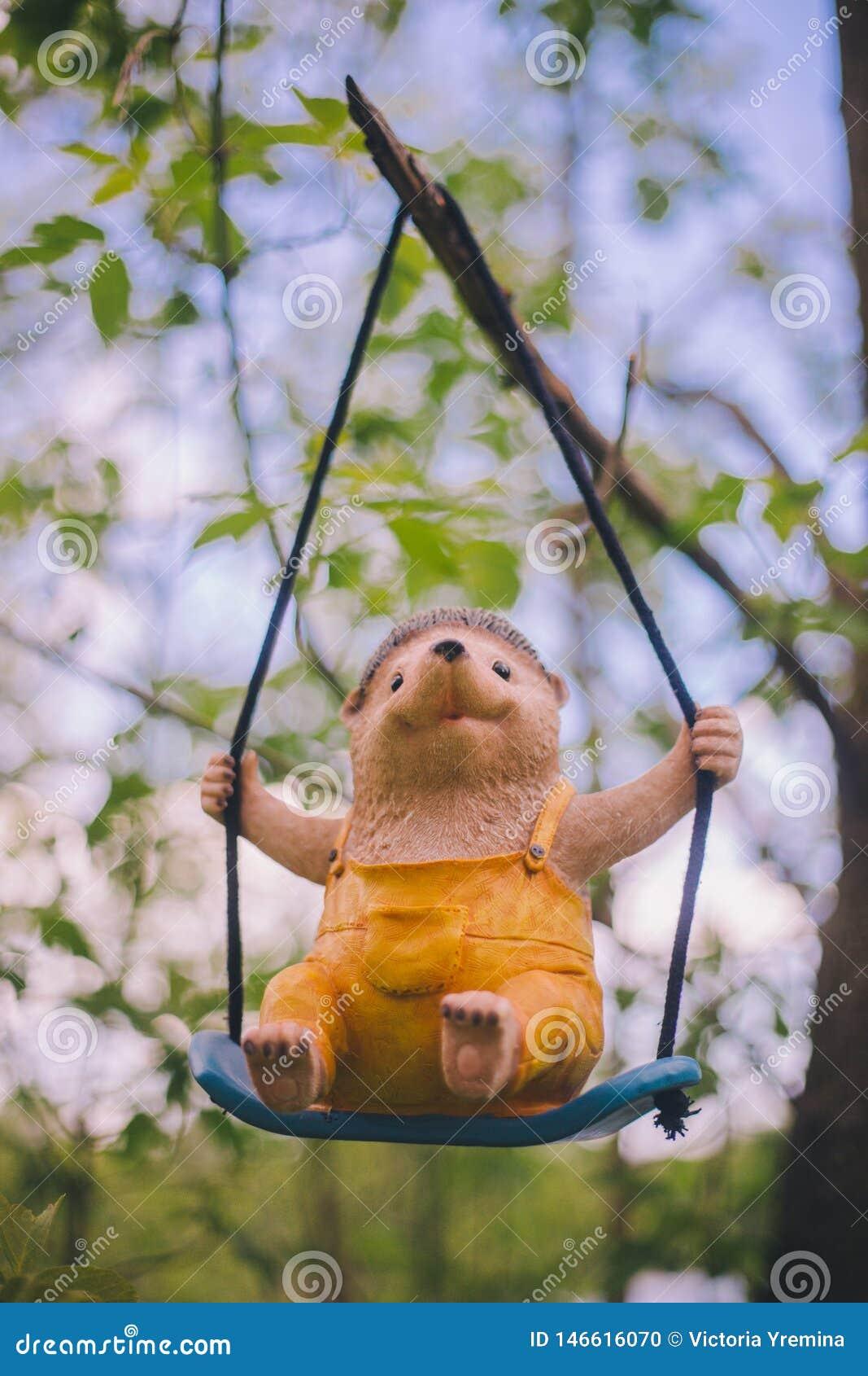Decora??o da estatueta do jardim do close-up - um ouri?o alegre na roupa amarela que se senta em um balan?o - que pendura em um r
