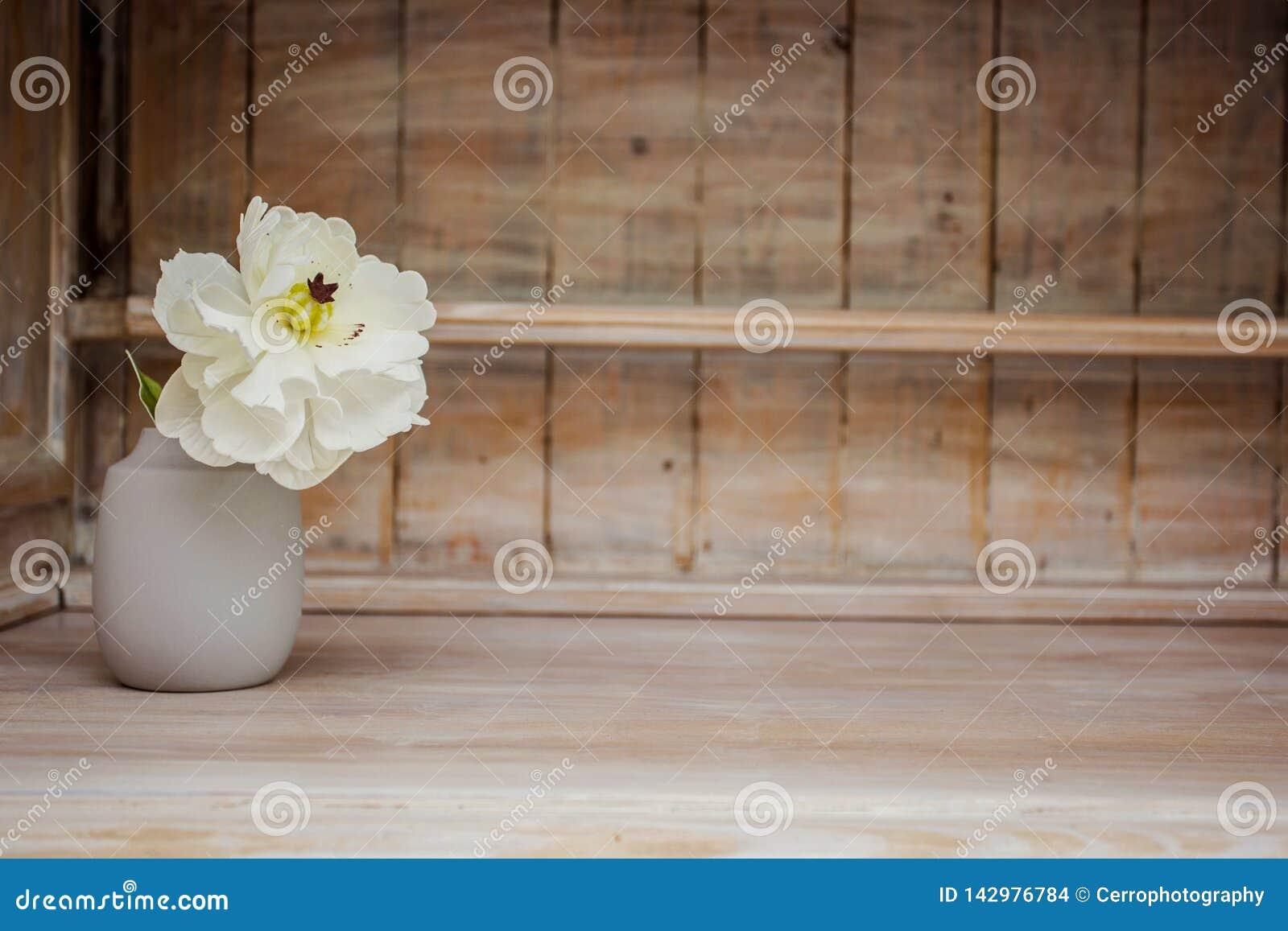 Decoración casera suave, florero con la pequeña flor blanca en un fondo de madera de la pared del vintage blanco y en un estante