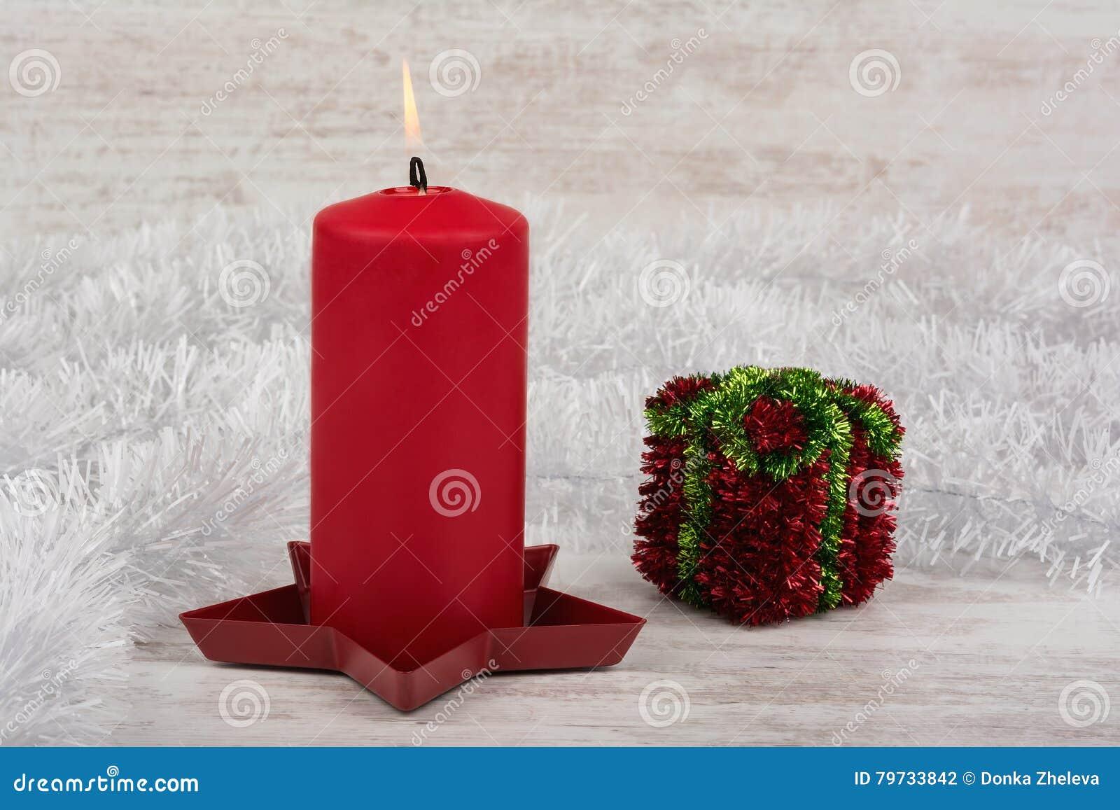 Decoración de la Navidad con la vela roja en el fondo de madera blanco