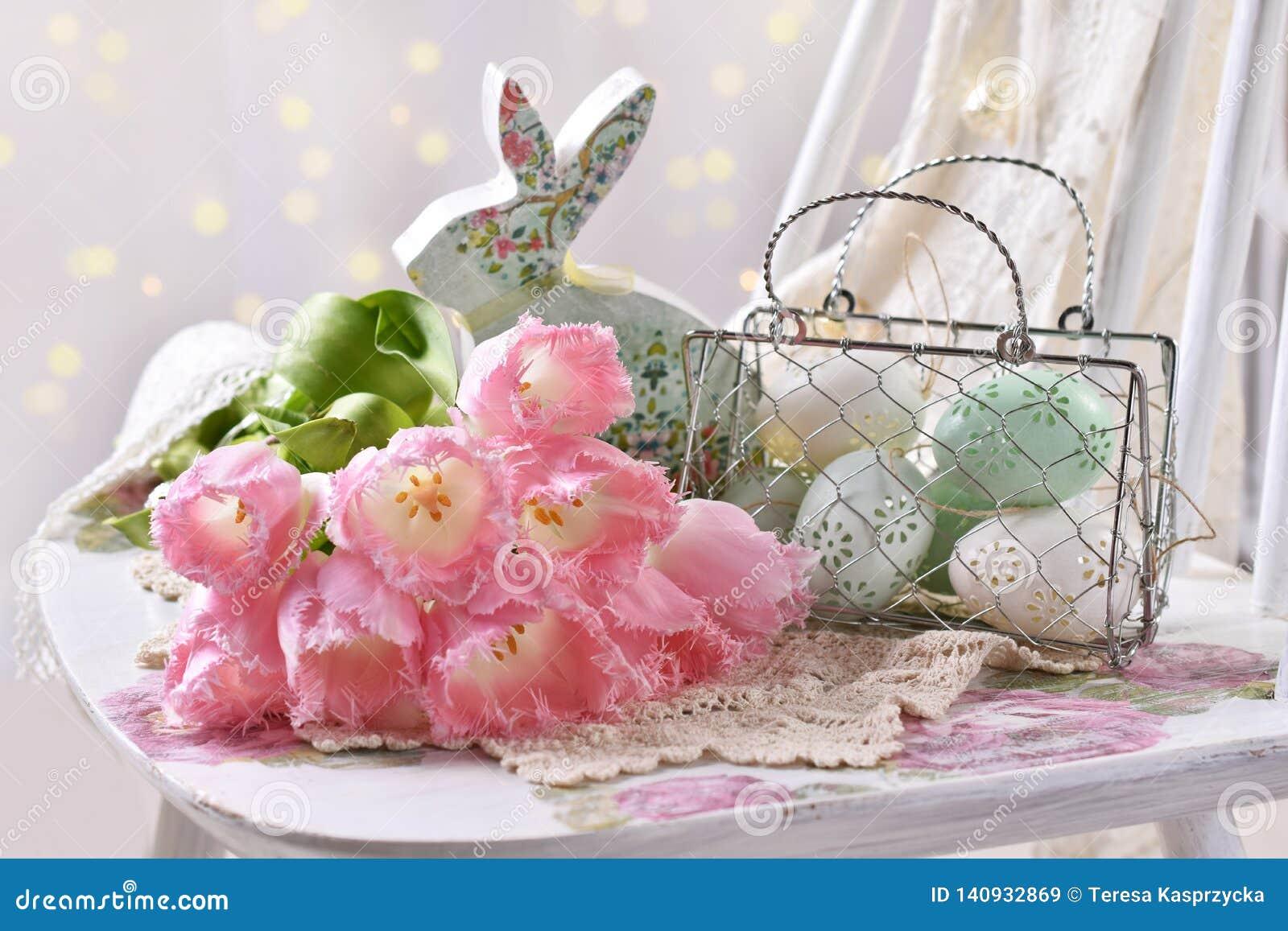 Decoración de Pascua con el manojo de huevos y de conejito rosados de los tulipanes