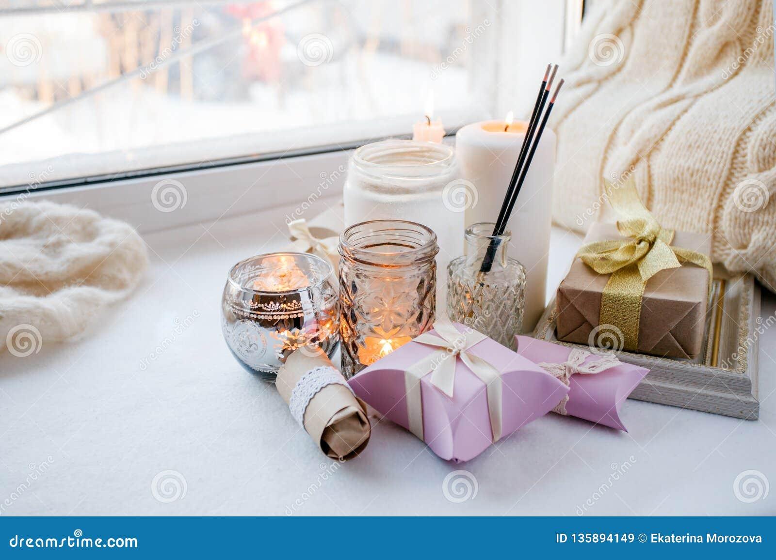 Decoración interior casera en colores marrones: tarro de cristal con el palillo del aroma, las velas y la caja de regalo romántic