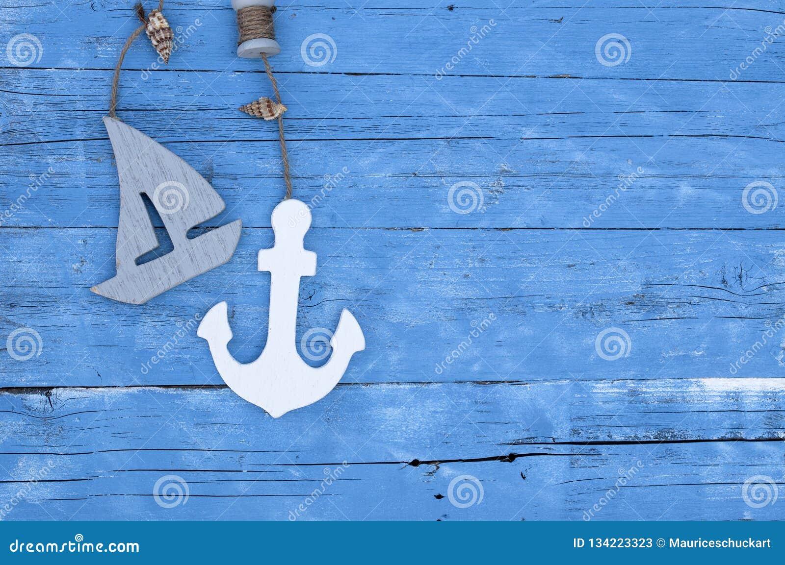 Decoración marítima con las cáscaras, estrellas de mar, velero, red de pesca en la madera azul de la deriva
