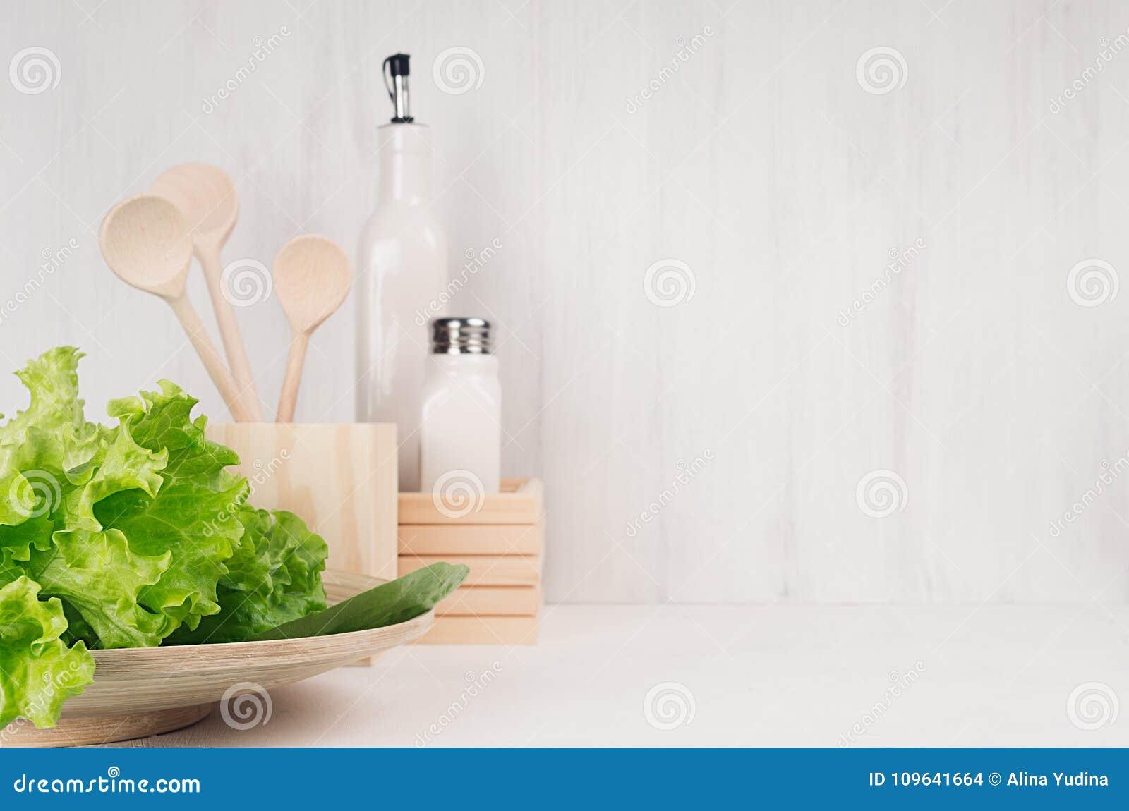 Decoración moderna blanca de la cocina con el plato de madera natural beige, utensilios, ensalada verde fresca en el fondo de mad