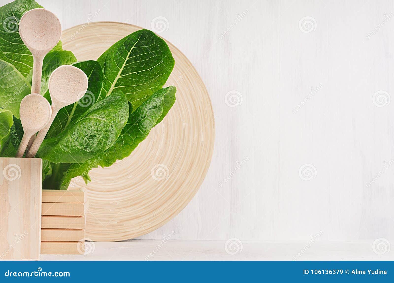 Decoración moderna de la cocina - el plato de madera beige, cucharas, verde se va en el fondo de madera blanco de la luz suave