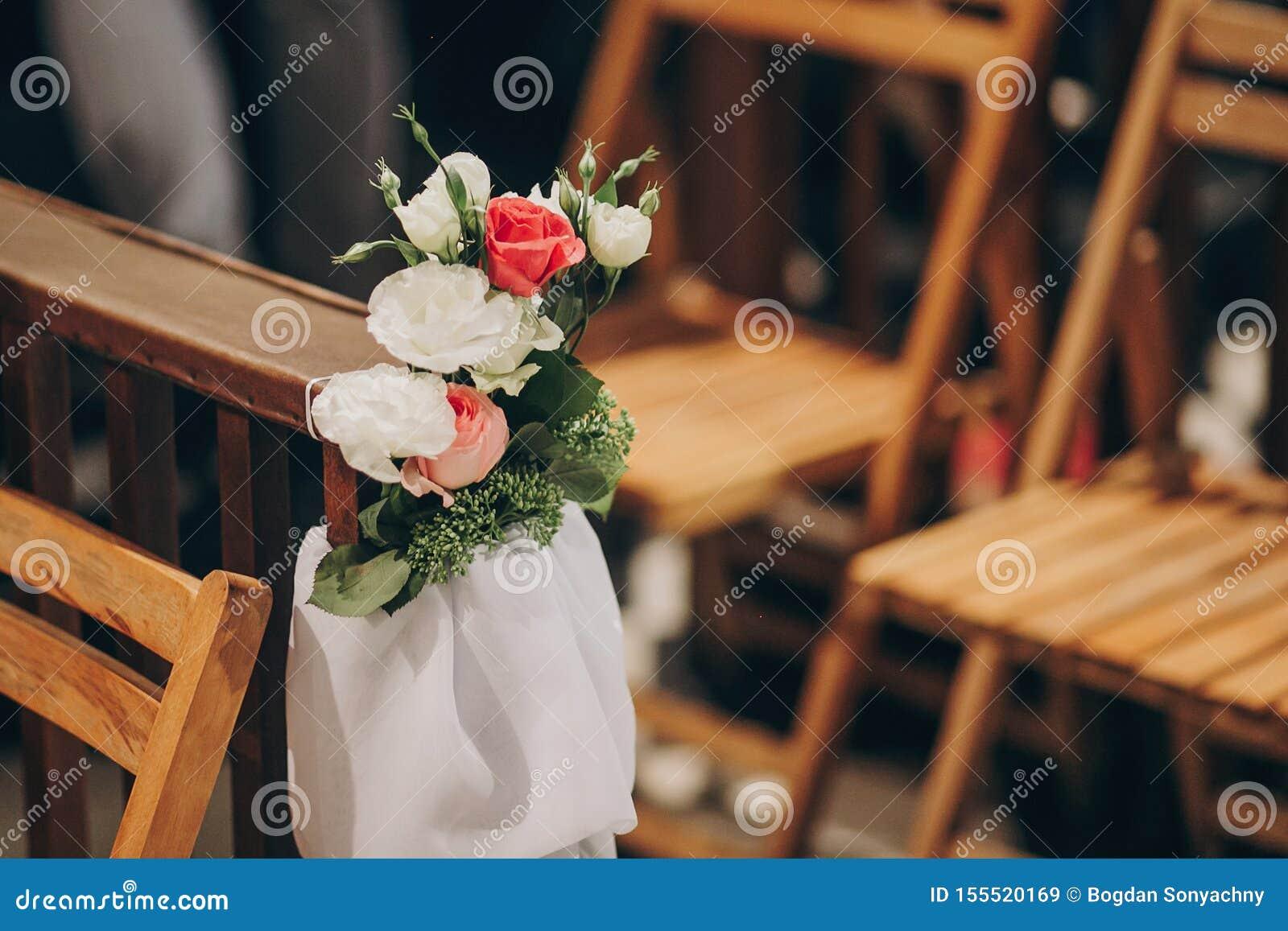 Decoración que se casa elegante de bancos de madera en la iglesia para el matrimonio santo Rosas y ramos hermosos de Tulle en sil