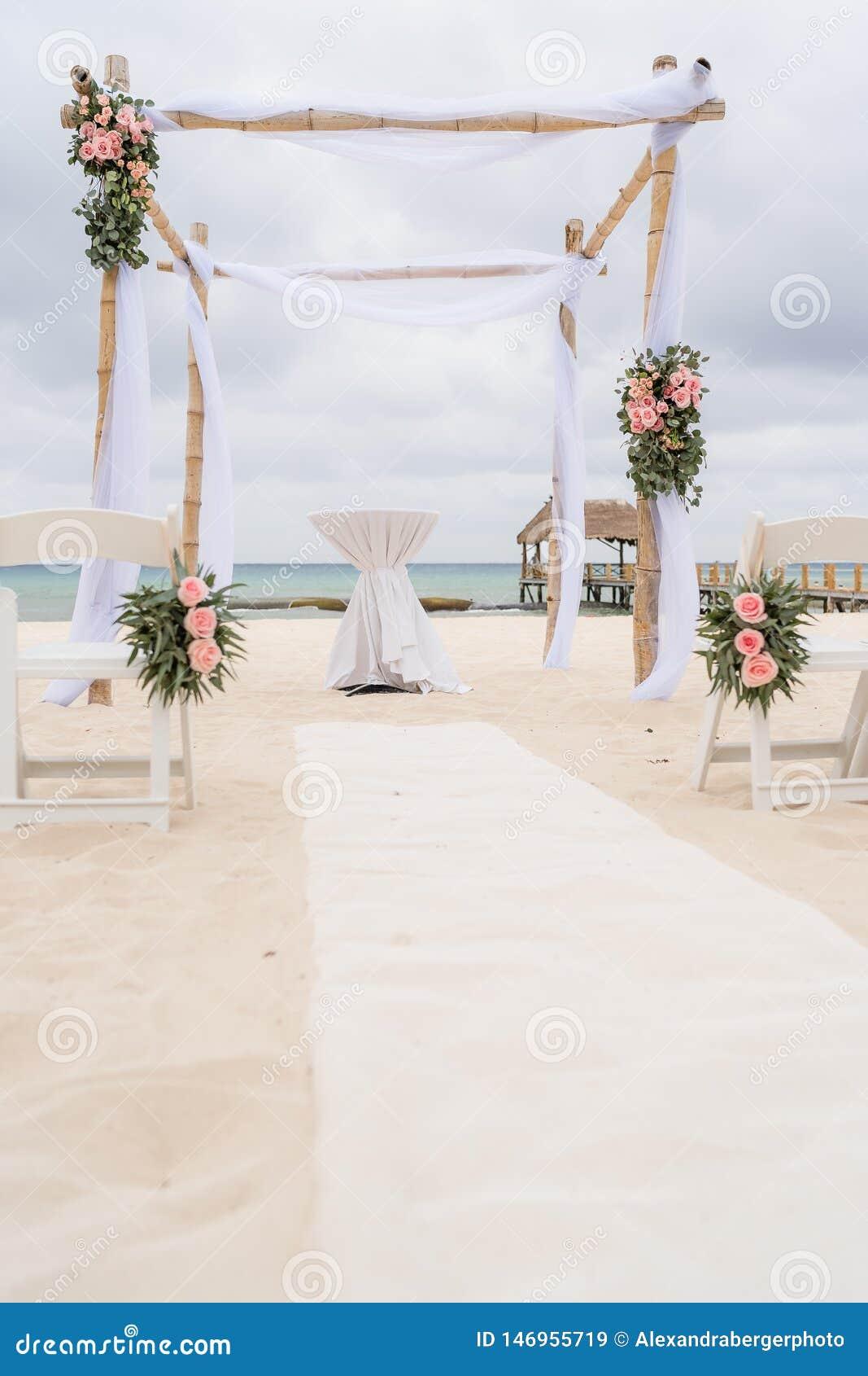 Decoración romántica de un pabellón de una boda de playa en la playa con el mar en el fondo y el cielo nublado