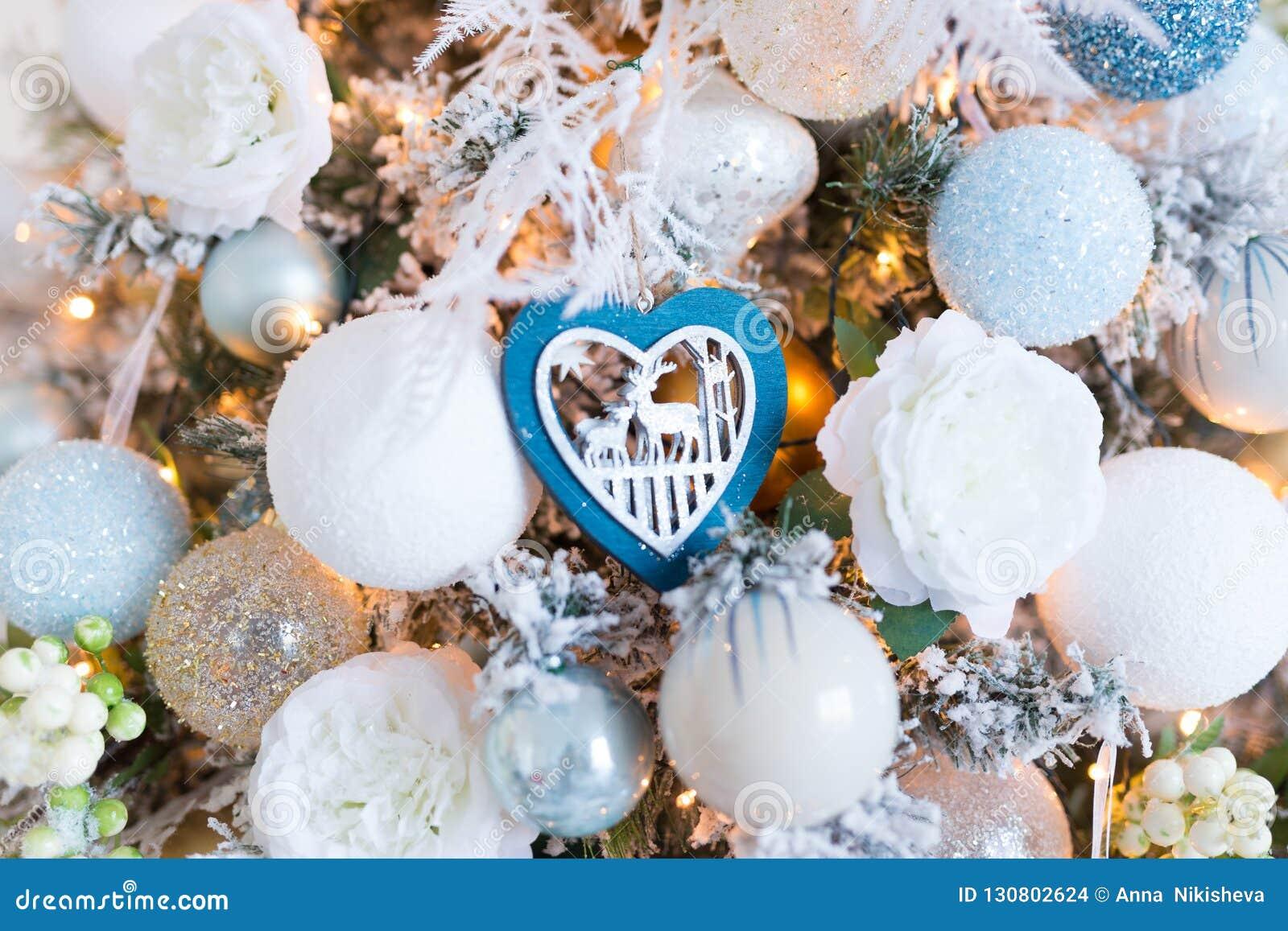 Decoraciones blancas del árbol de navidad en un piel-árbol de la Navidad
