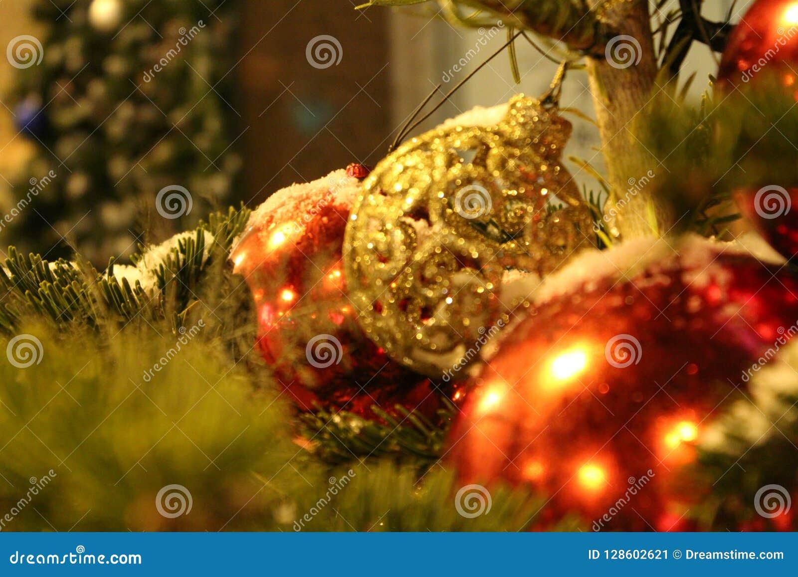 Decoraciones de la Navidad en el árbol de navidad en rojo y colores oro bajo la forma de primer de las bolas En la calle o en la