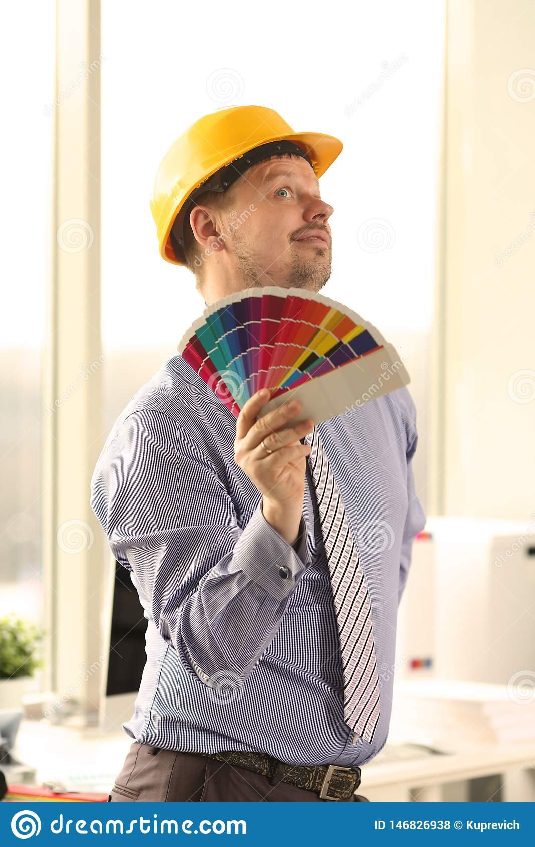 Decorador caucasiano masculino que guarda amostras de folha da cor