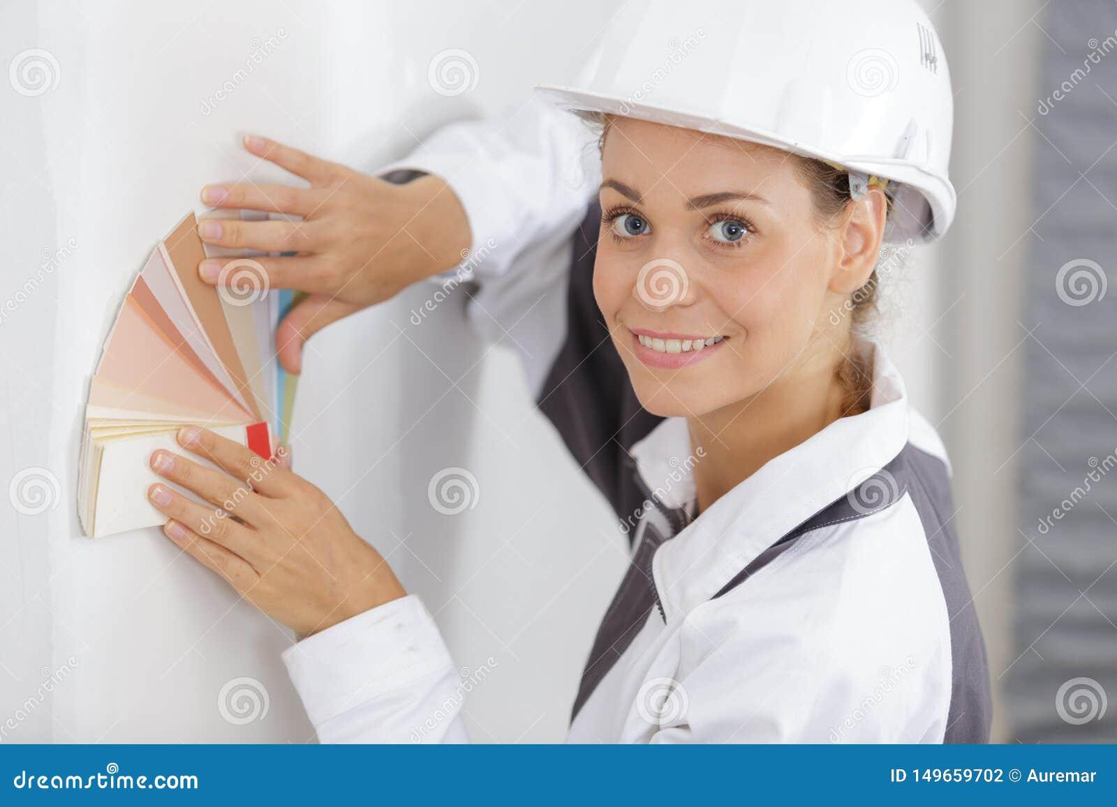 Decorador de sexo femenino que lleva a cabo la carta de la pintura contra la pared