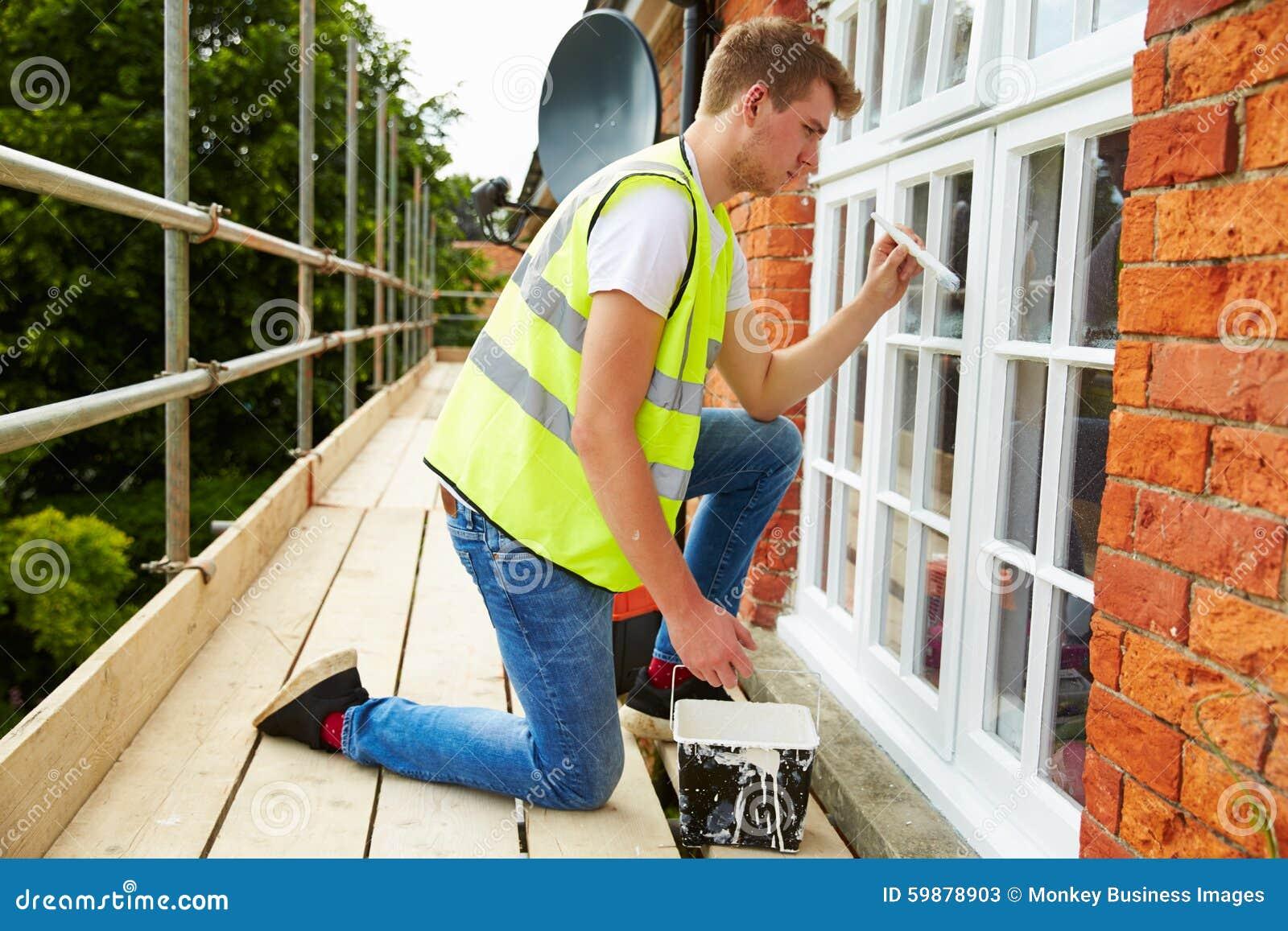Decorador en el andamio que pinta la casa exterior Windows