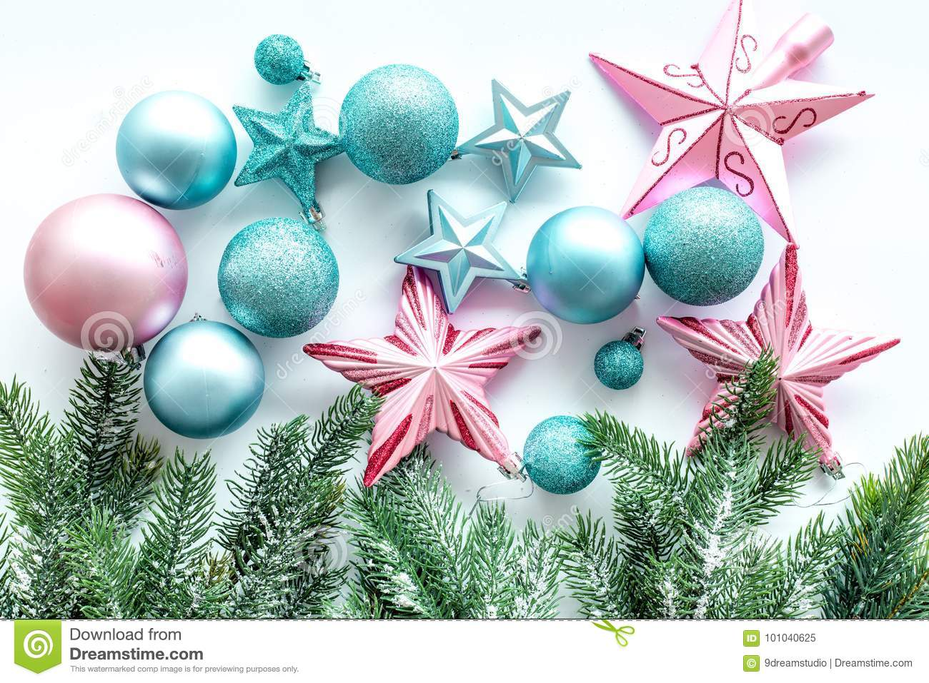 decorate the christmas tree pink and blue stars and balls near pine branches on white