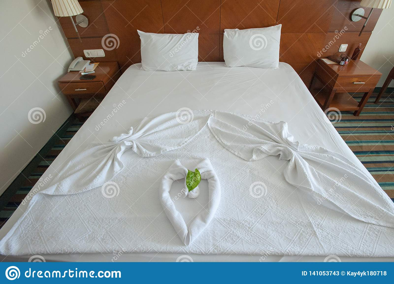 Decorated bed with towels and heart-shaped covers