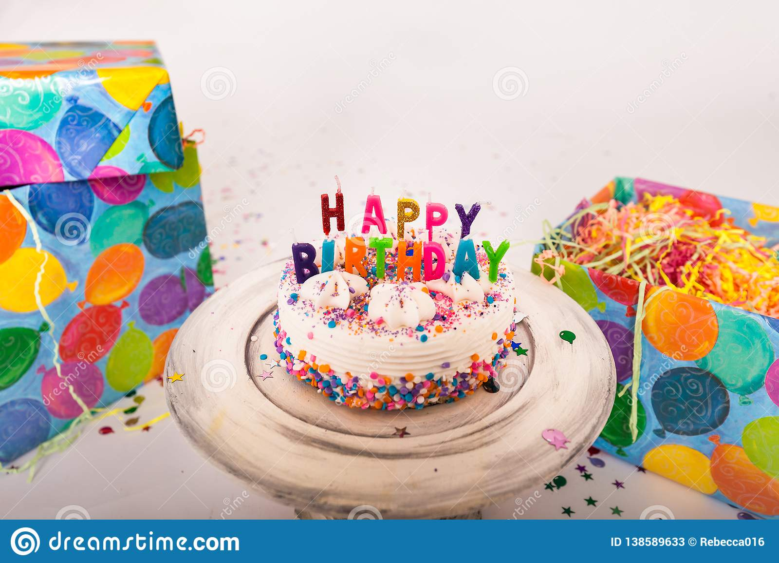 Decorated Birthday Cake Happy Candles On Stand Balloon Wrapping Paper Wrapped Gifts Solid Background