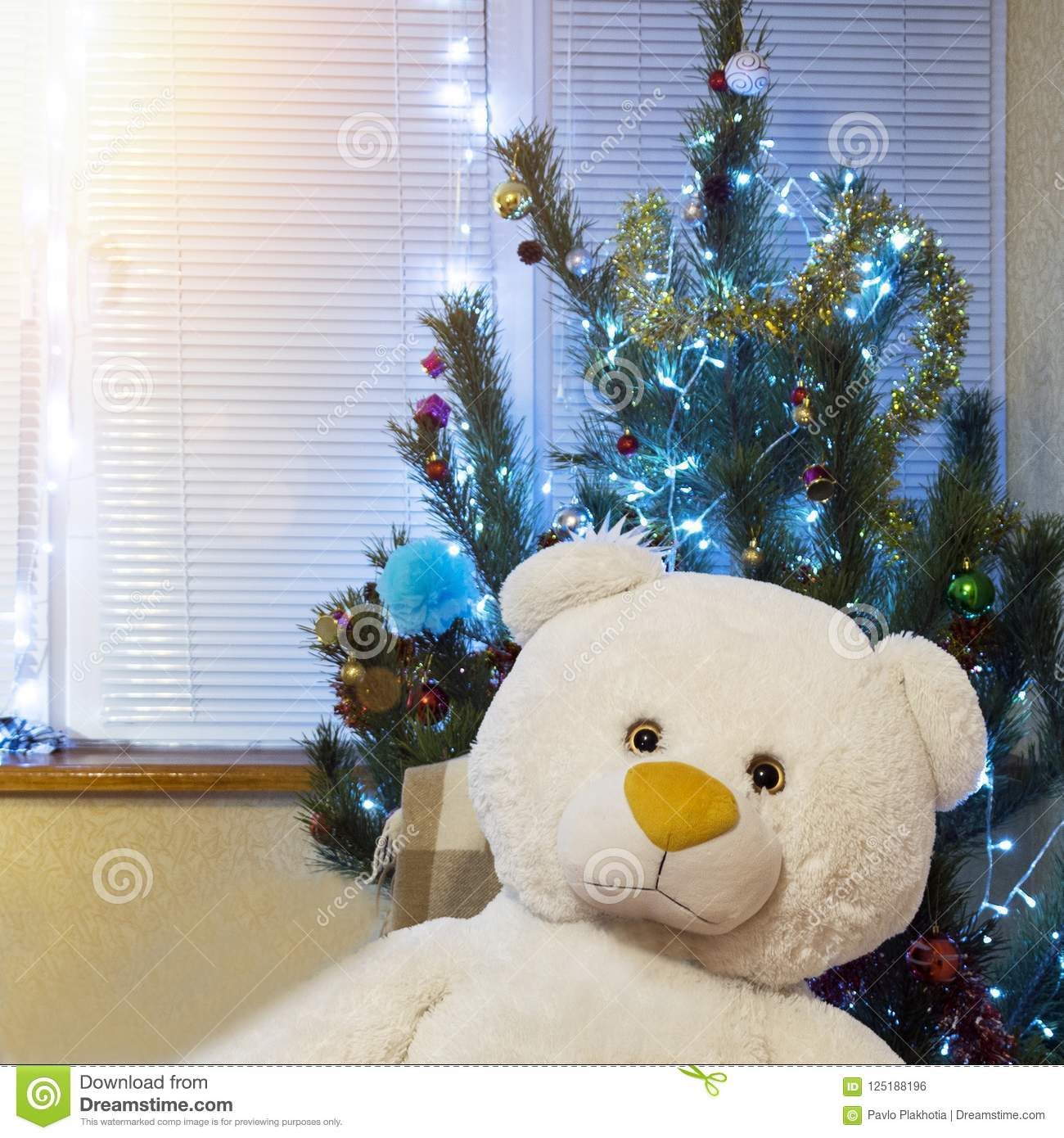 Decorated Christmas tree and big teddy bear. Cute New Year present under shining pine