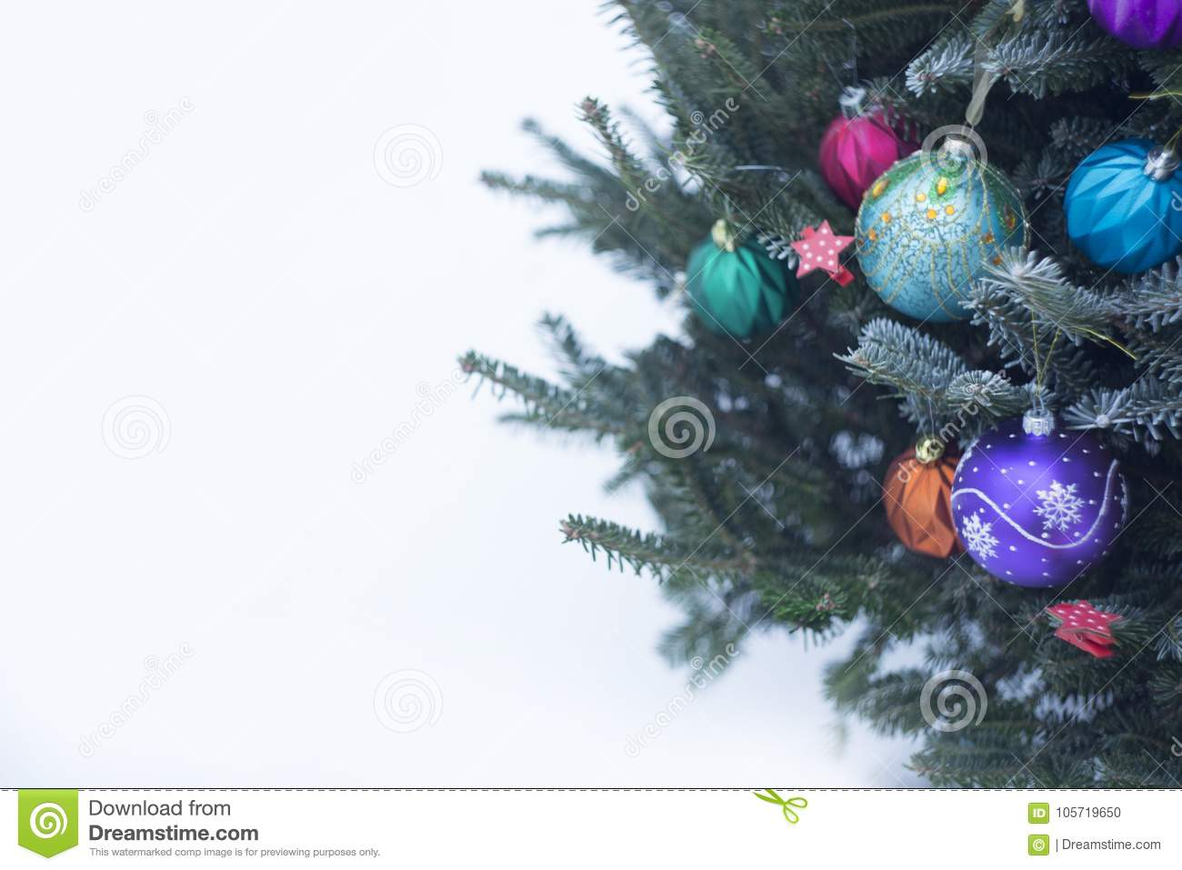 A decorated Christmas tree outside with colorful baubles made of glass