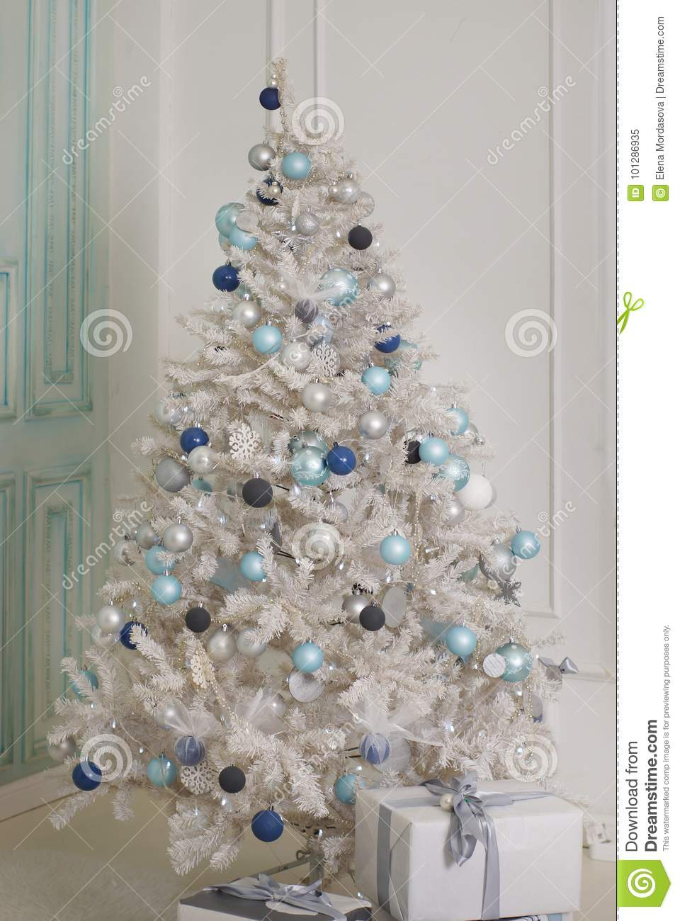 download a decorated christmas tree stands near a bright wall artificial white spruce with blue