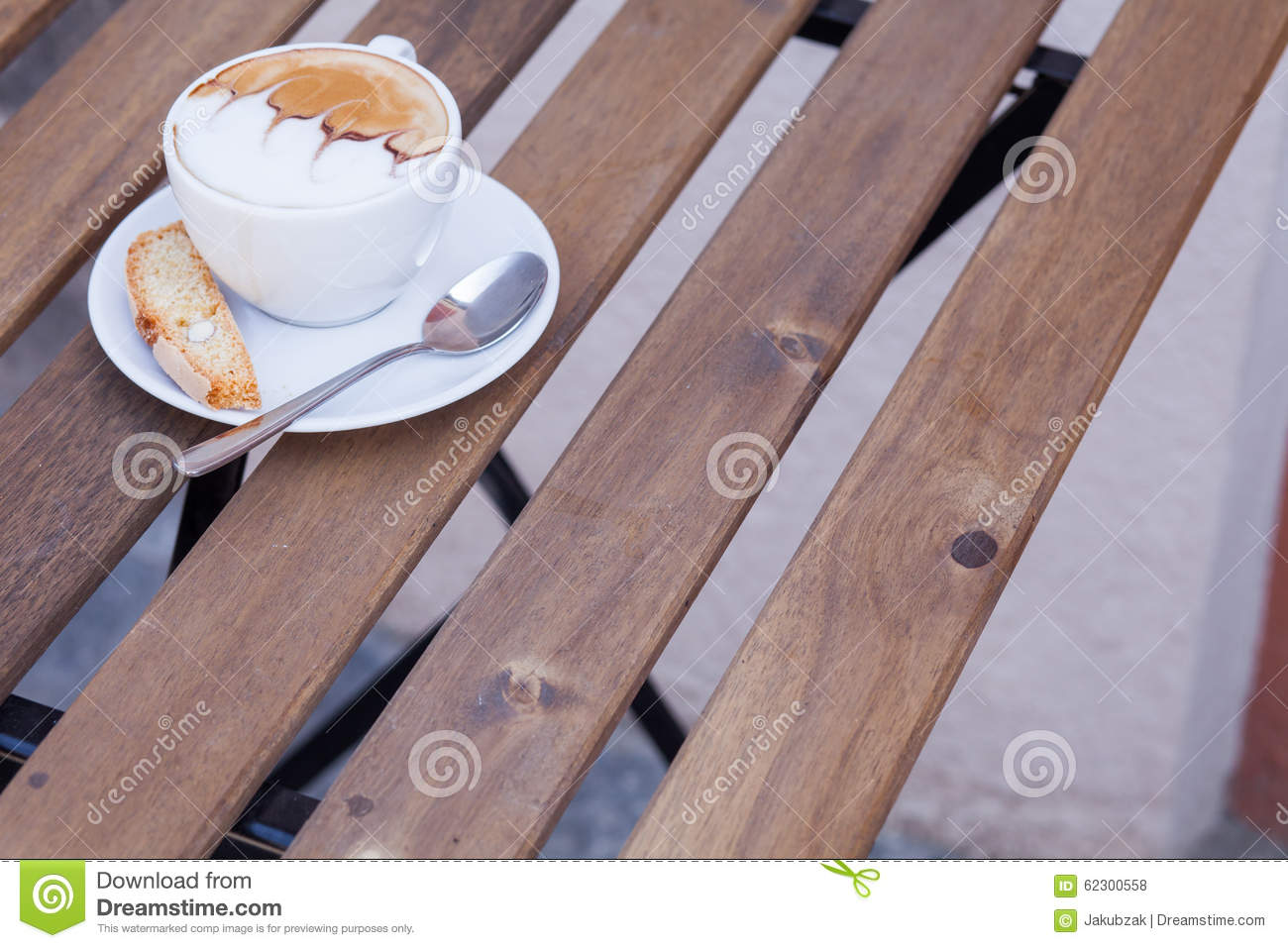 Decorated coffee with cookie and spoon on a wooden table