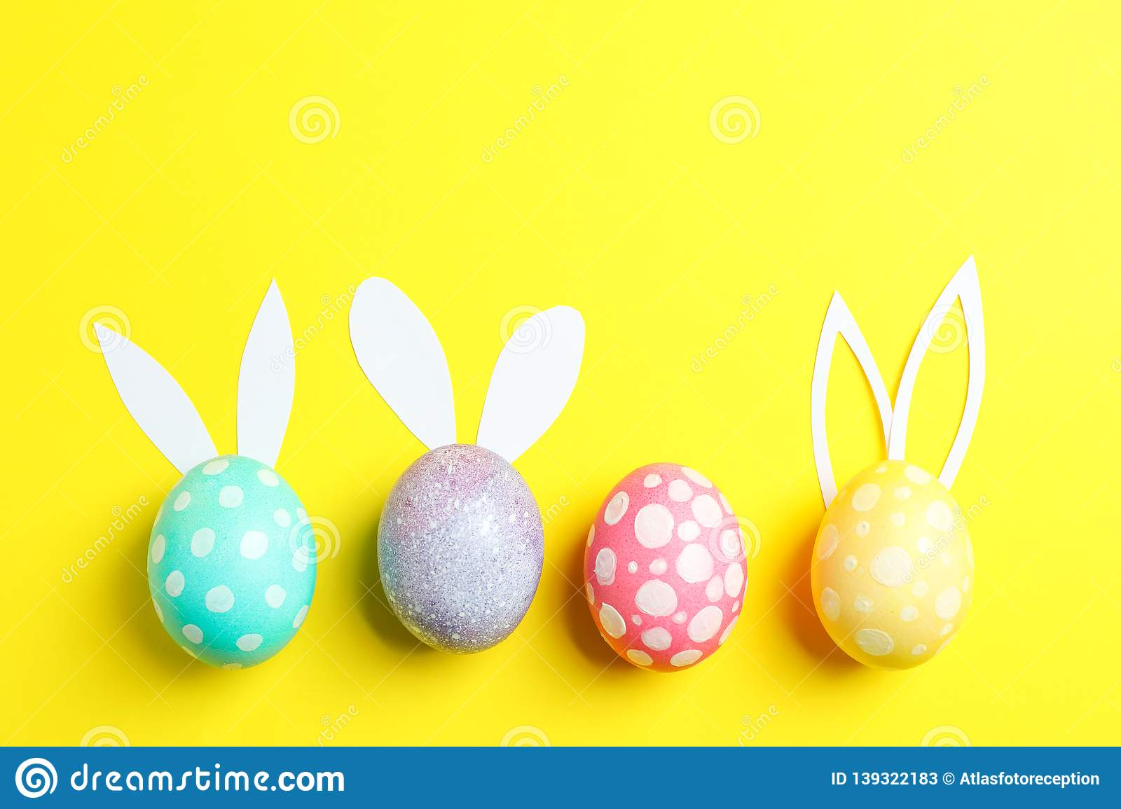 Decorated Easter eggs with cute bunnies ears on yellow background