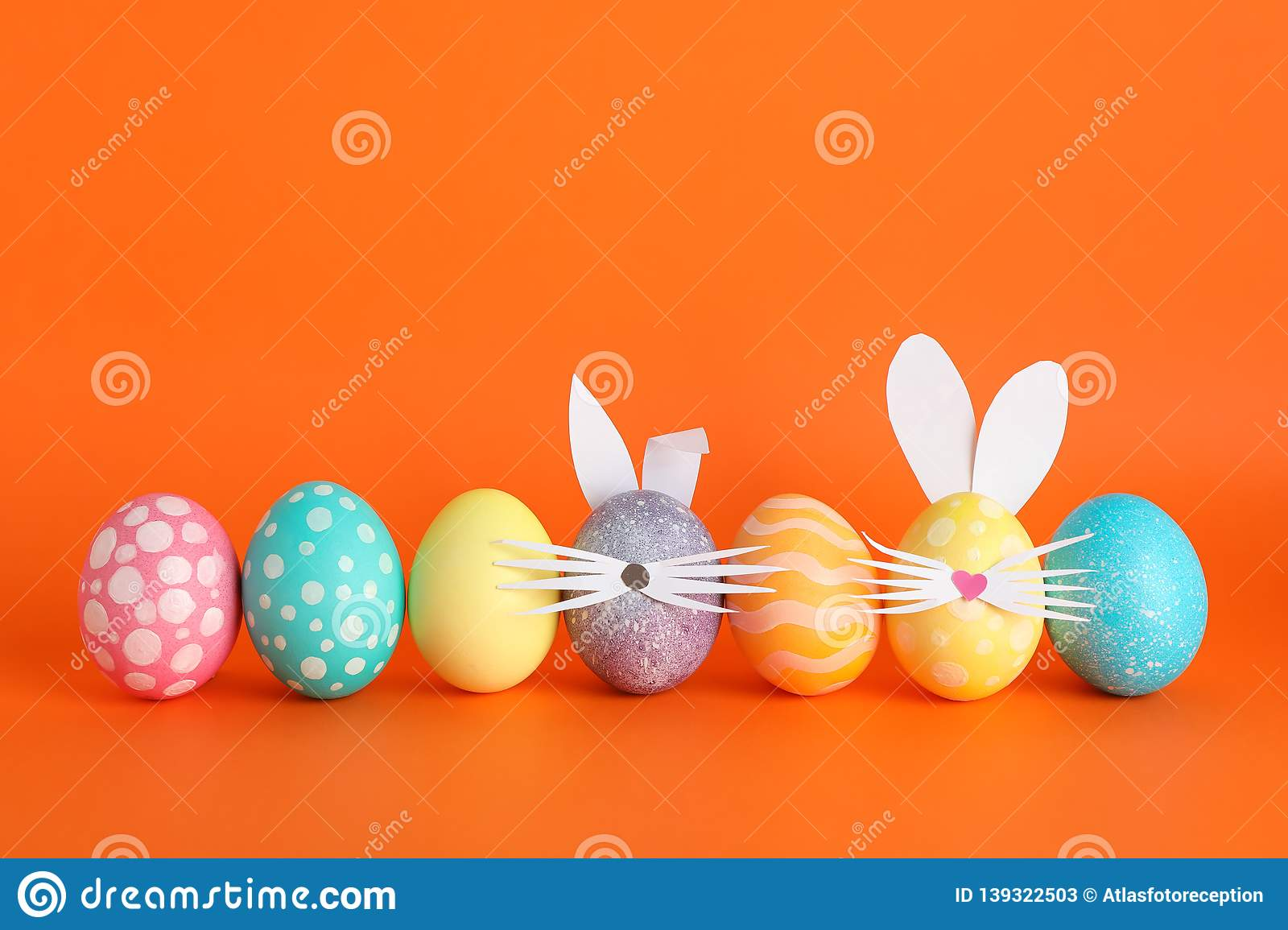 Decorated Easter eggs and cute bunny`s ears on background