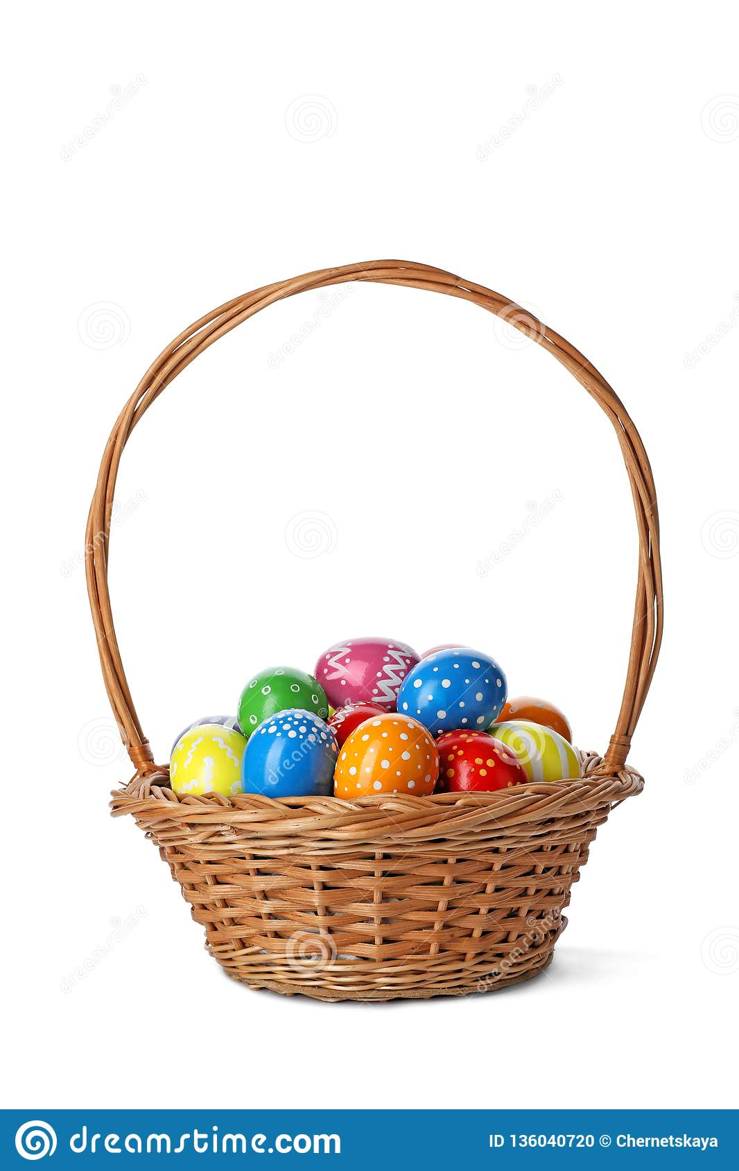 Decorated Easter eggs in wicker basket on white