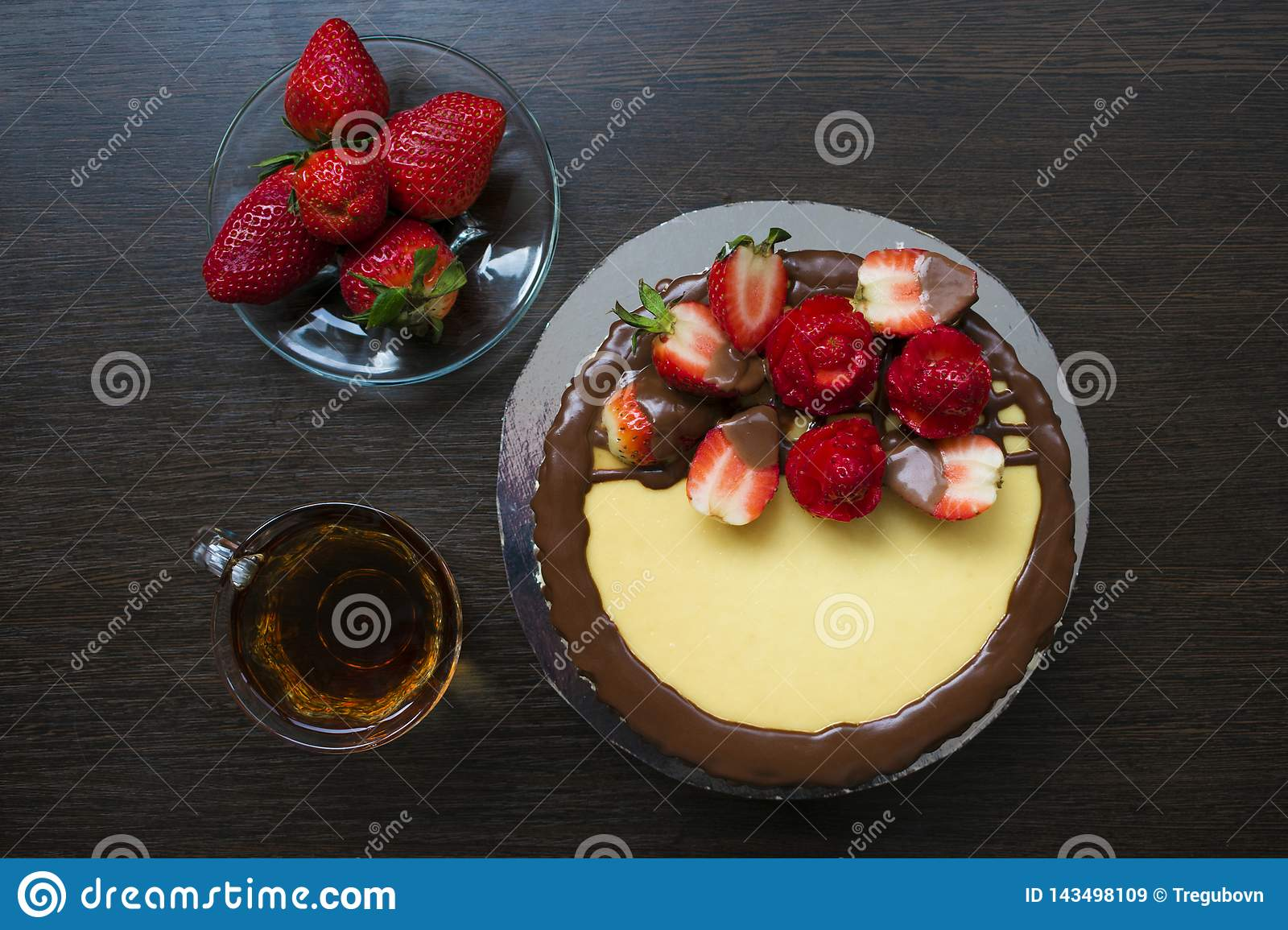 Strawberries on a saucer on the background of a wooden standDecorated strawberry cheesecake with a cup of tea and strawberries